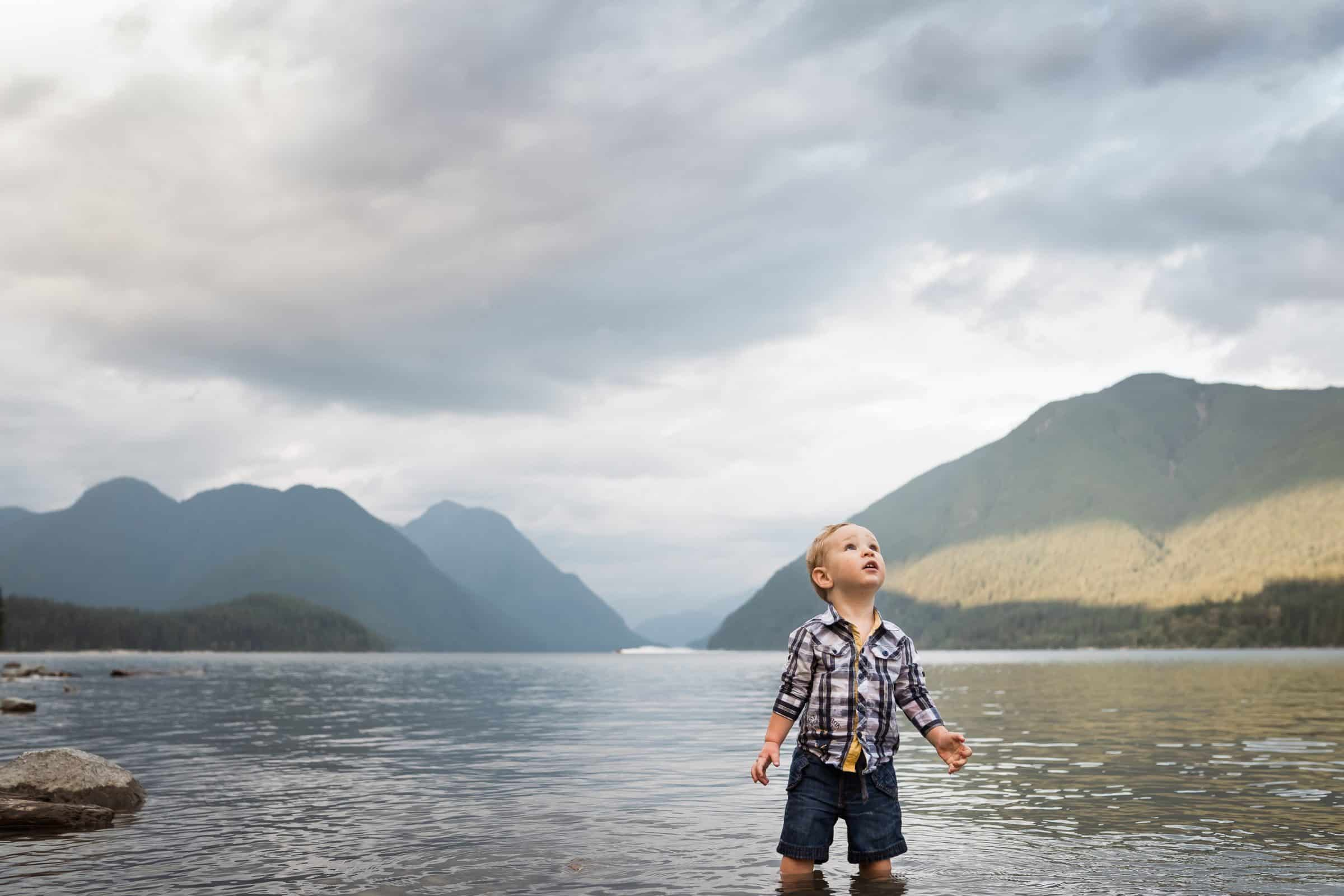 toddler boy standing in lake looking at the sky