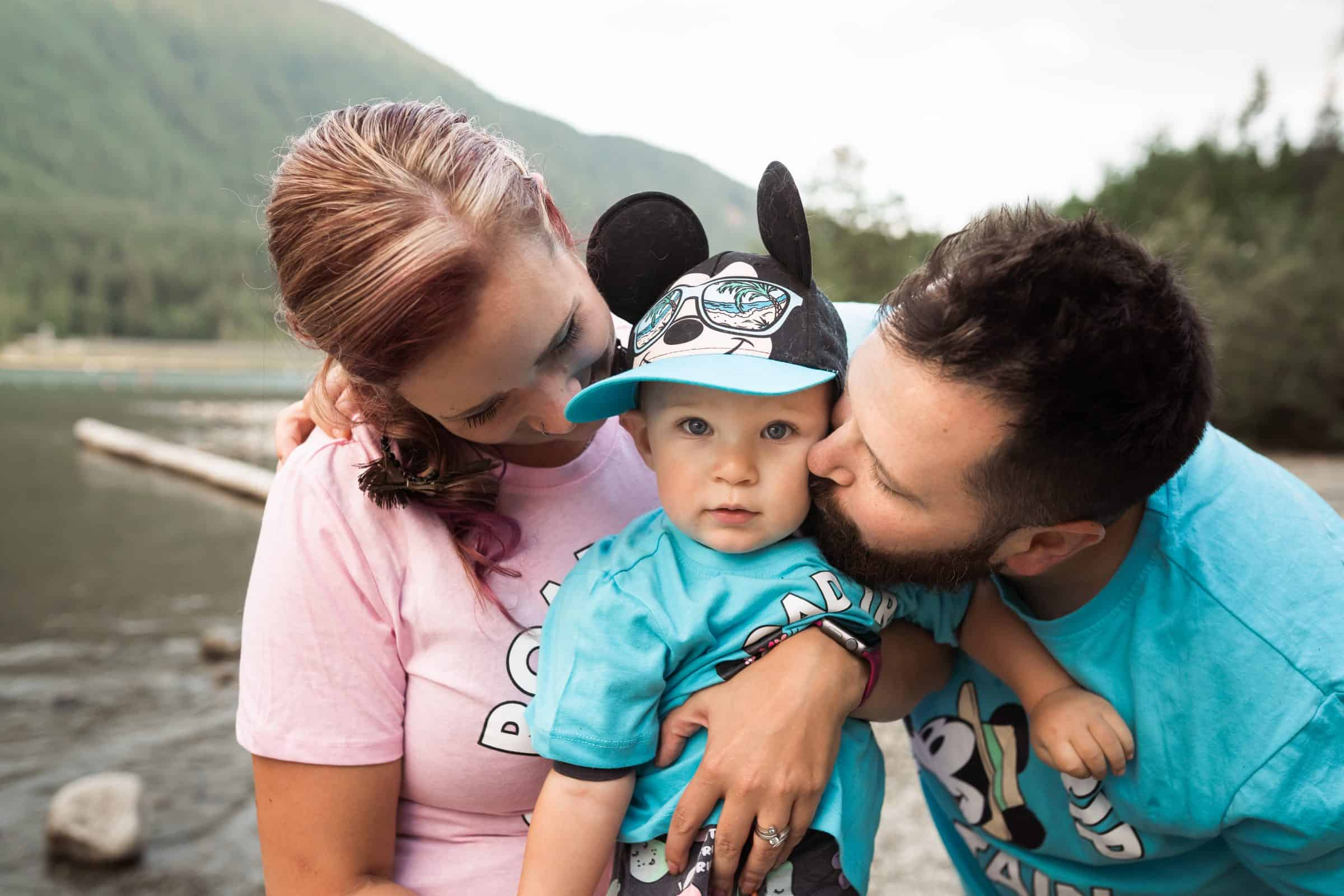 mom and dad kissing toddler boy in disney clothing