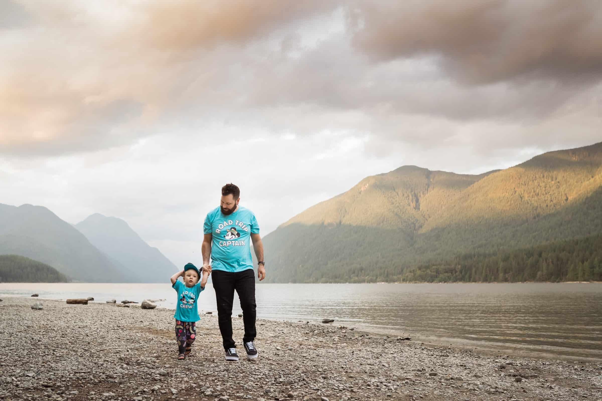dad walking toddler boy alongside a lake in disney clothing