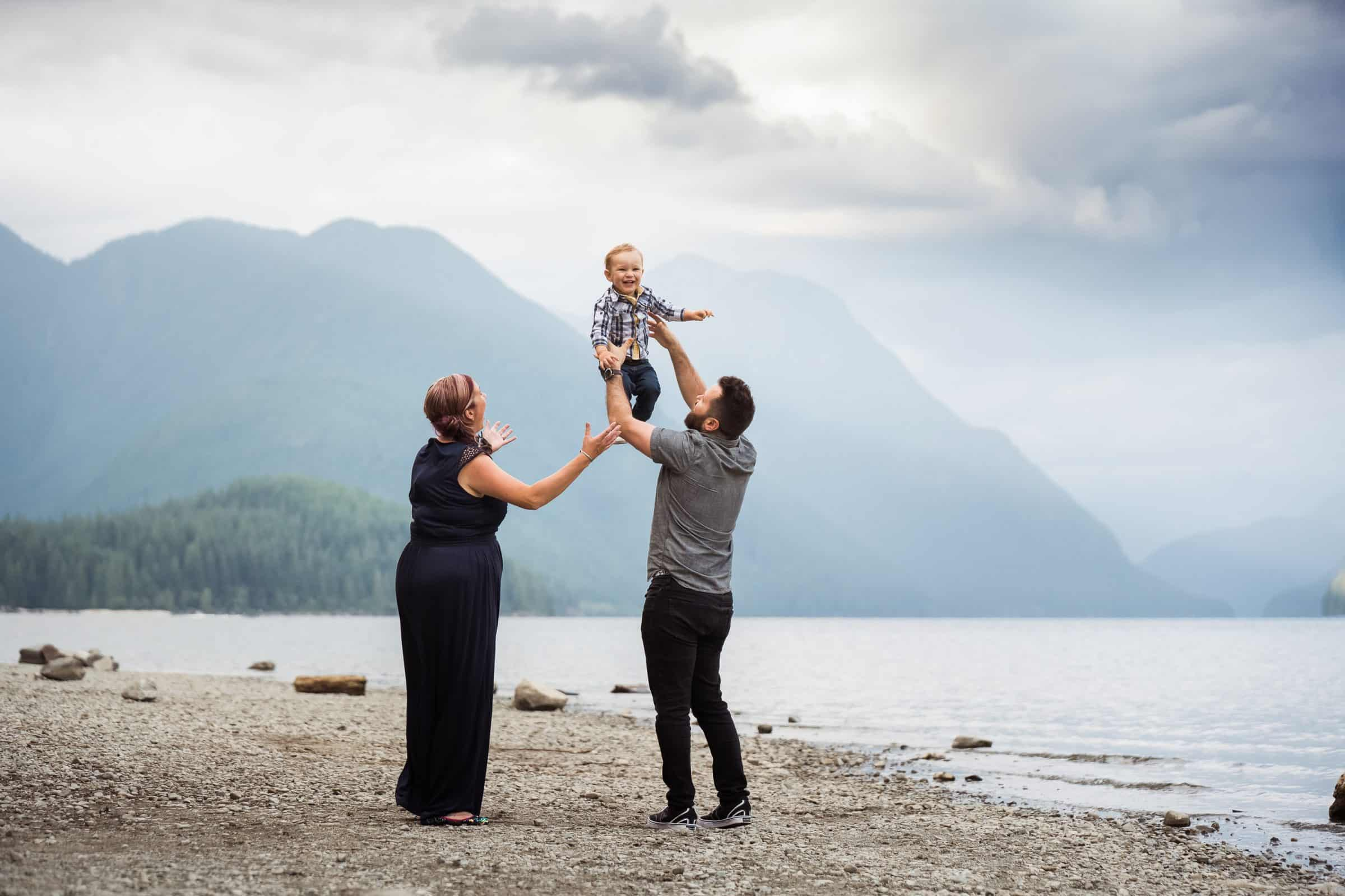 dad throwing little boy in arm beside mom with lake and mountains in the background