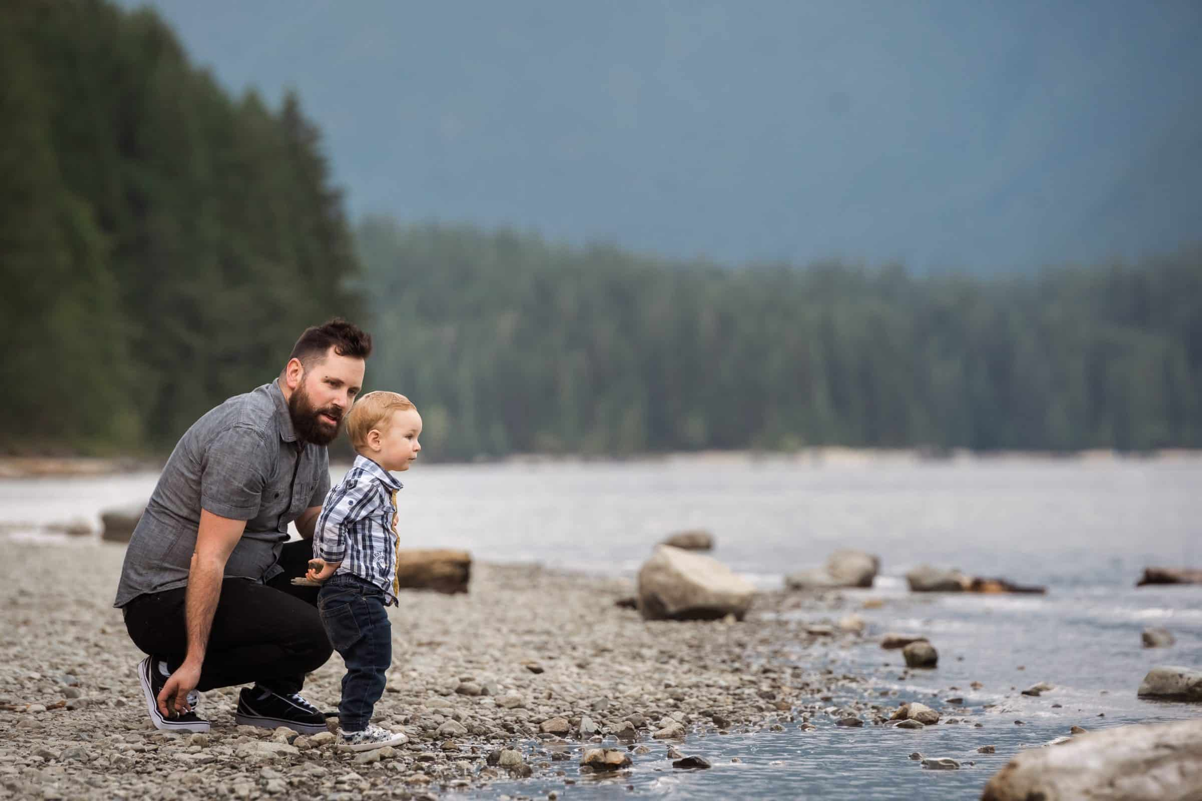 father and son throwing rocks by lake's edge