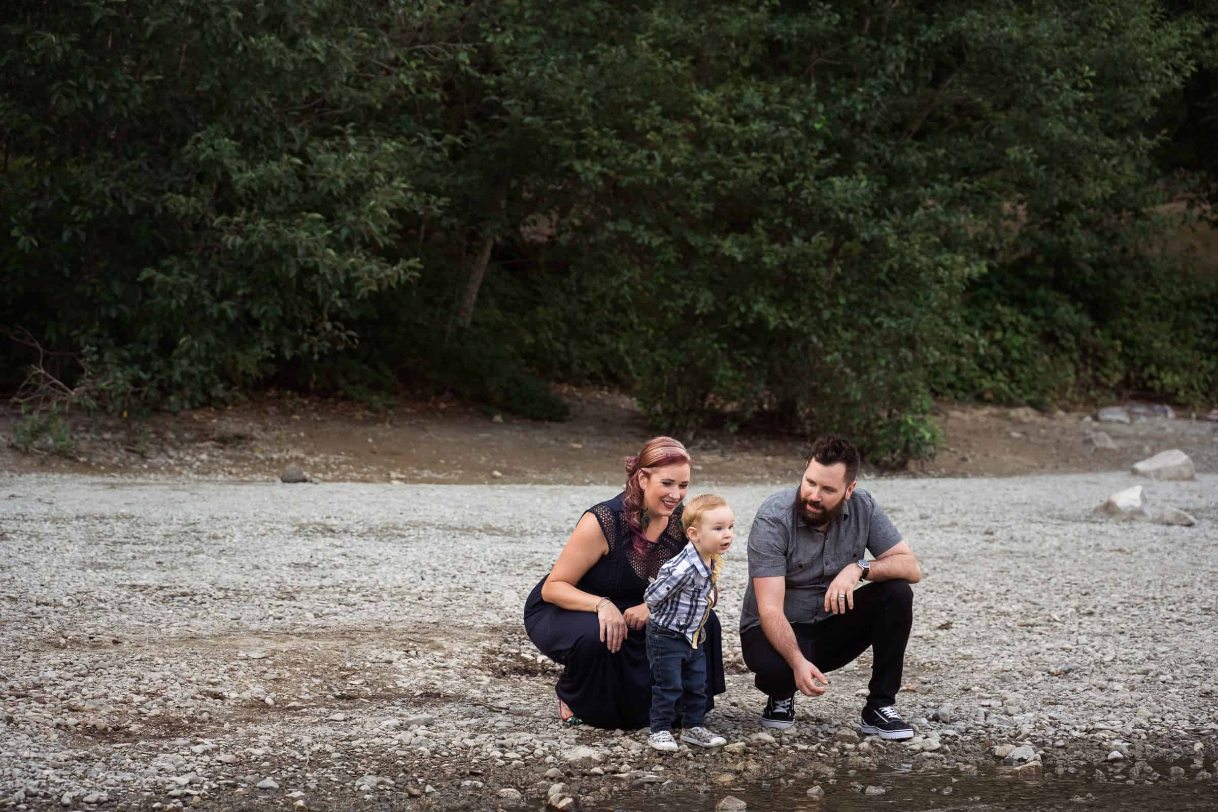 family squatting by edge of lake with toddler throwing rocks