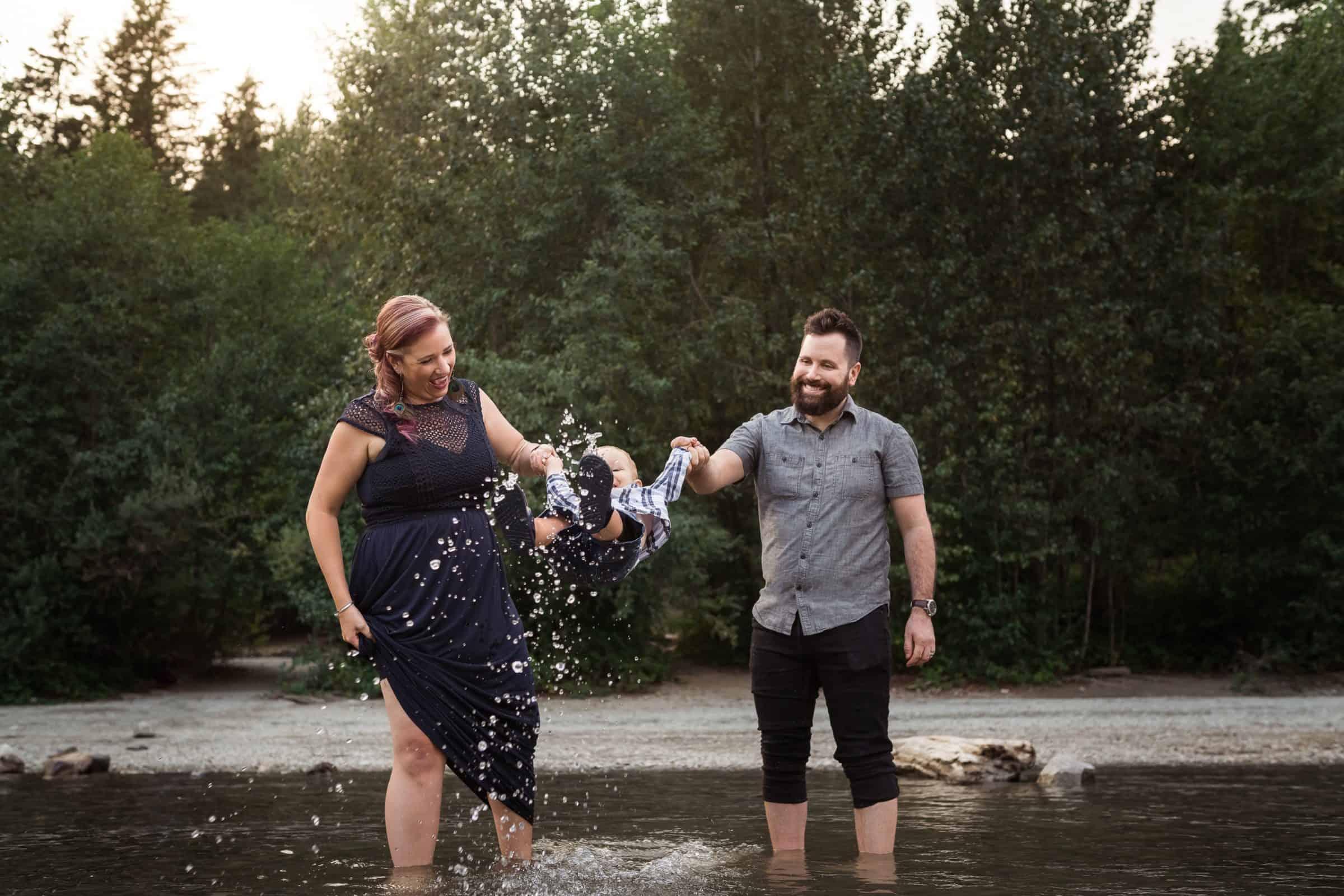 parents swinging and splashing toddler in lake
