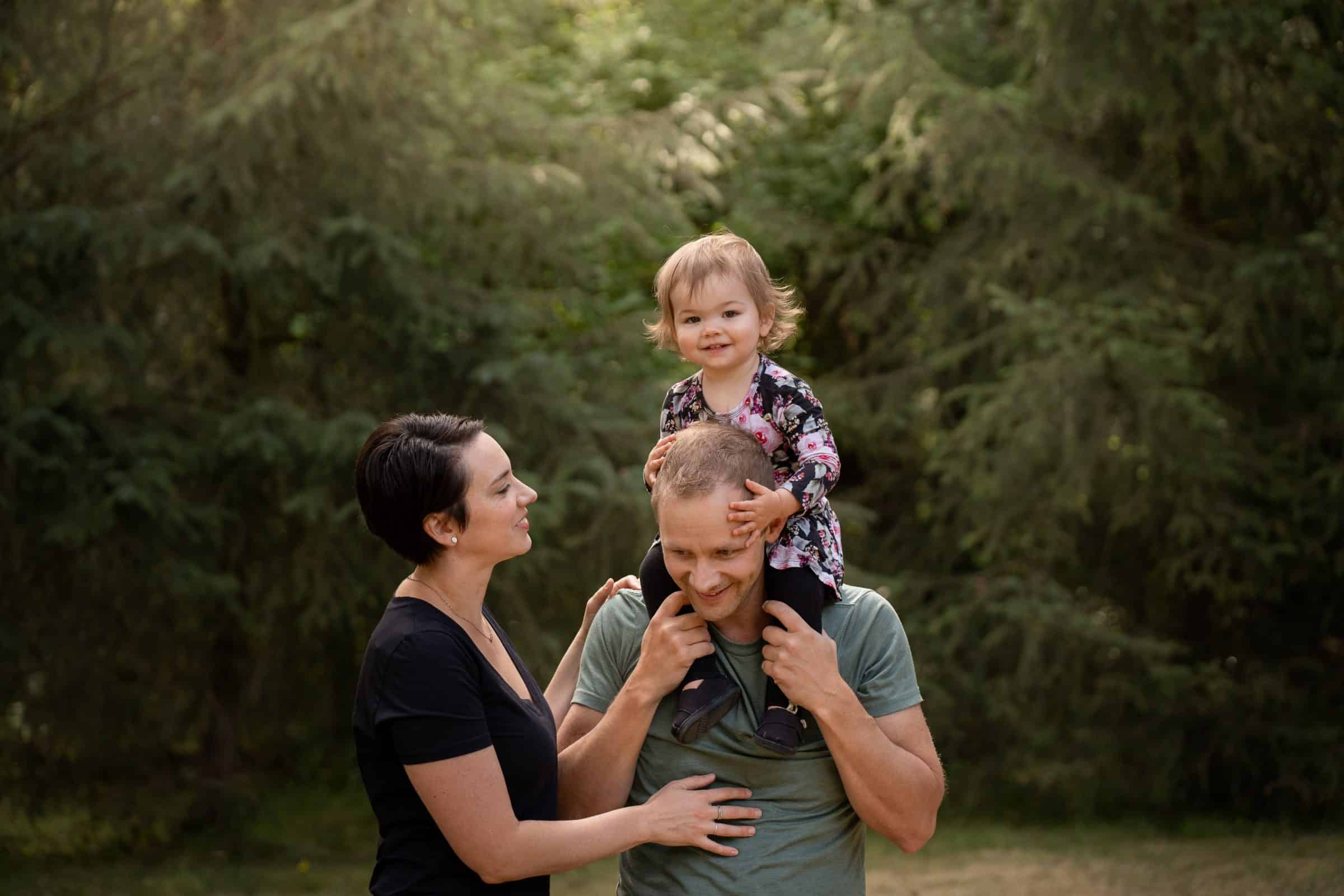 family photo with toddler girl on dad's shoulders smiling at camera
