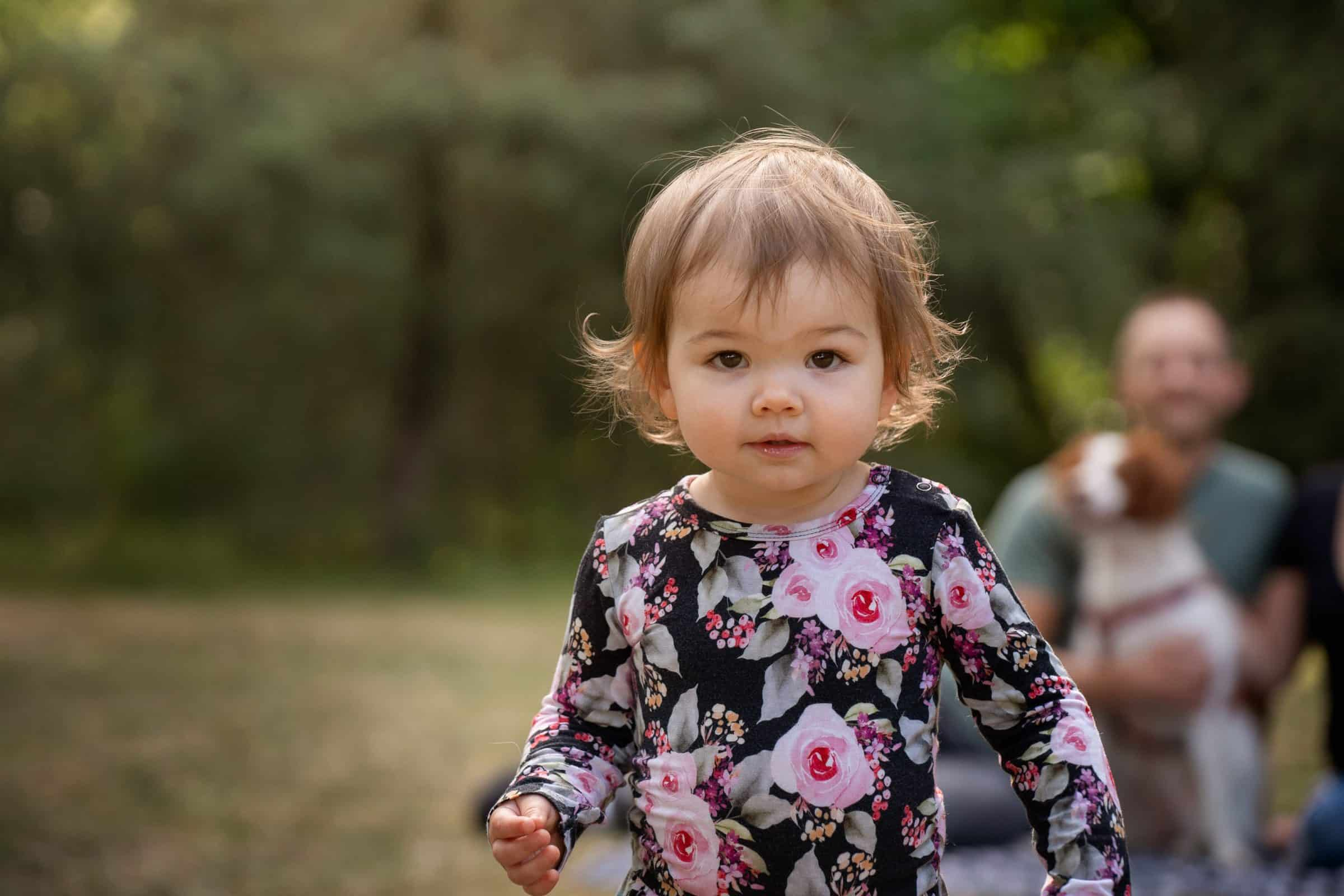 close up of toddler girl with family blurred in background