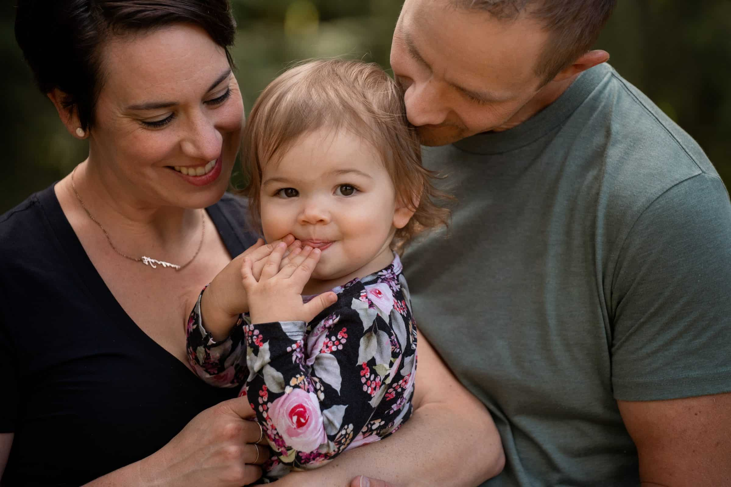 mom and dad holding toddler girl as she looks at camera