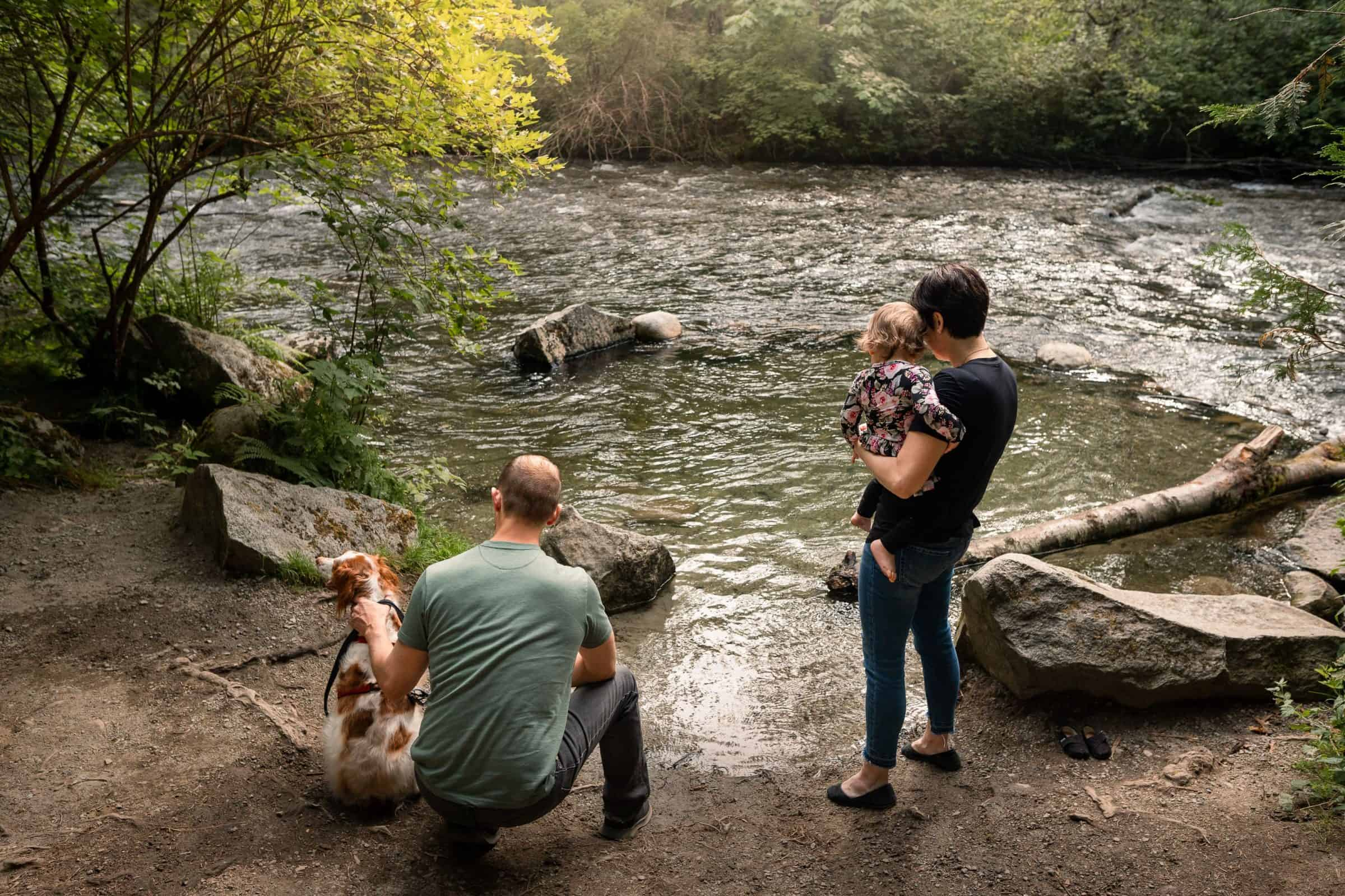 family with dog playing near river edge