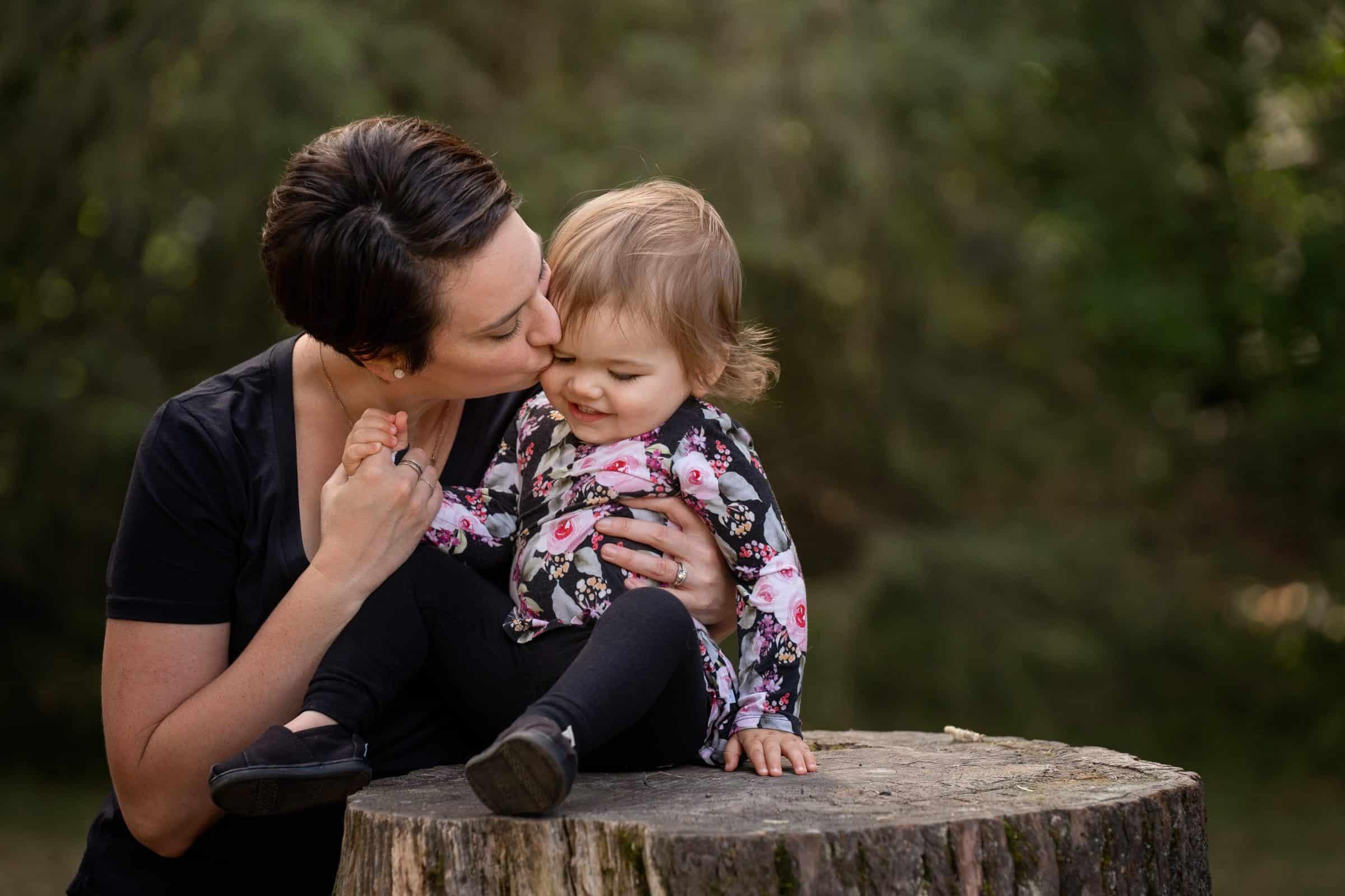 mom kissing toddler girl sitting on stump