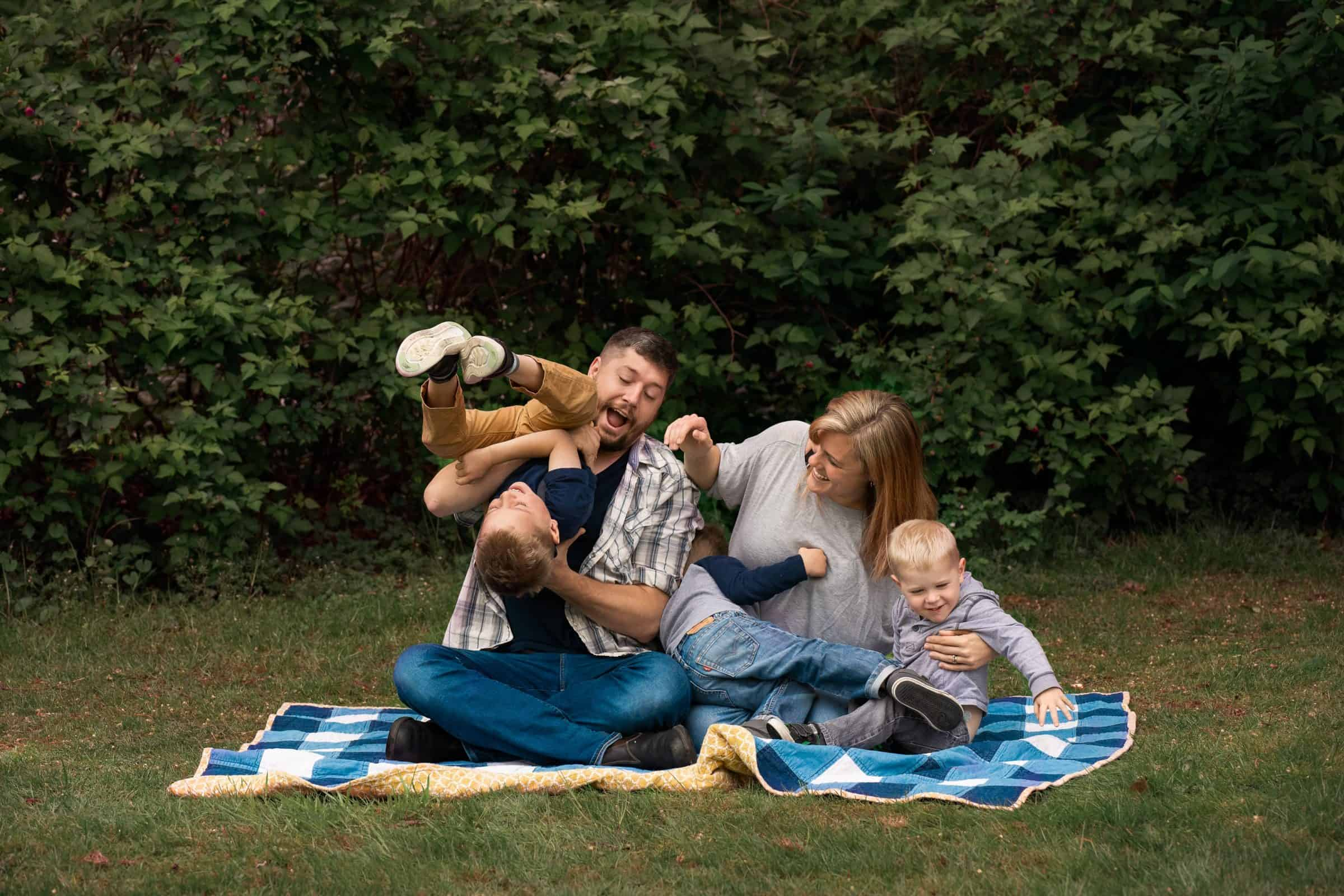 family photo of parents with three little boys wrestling