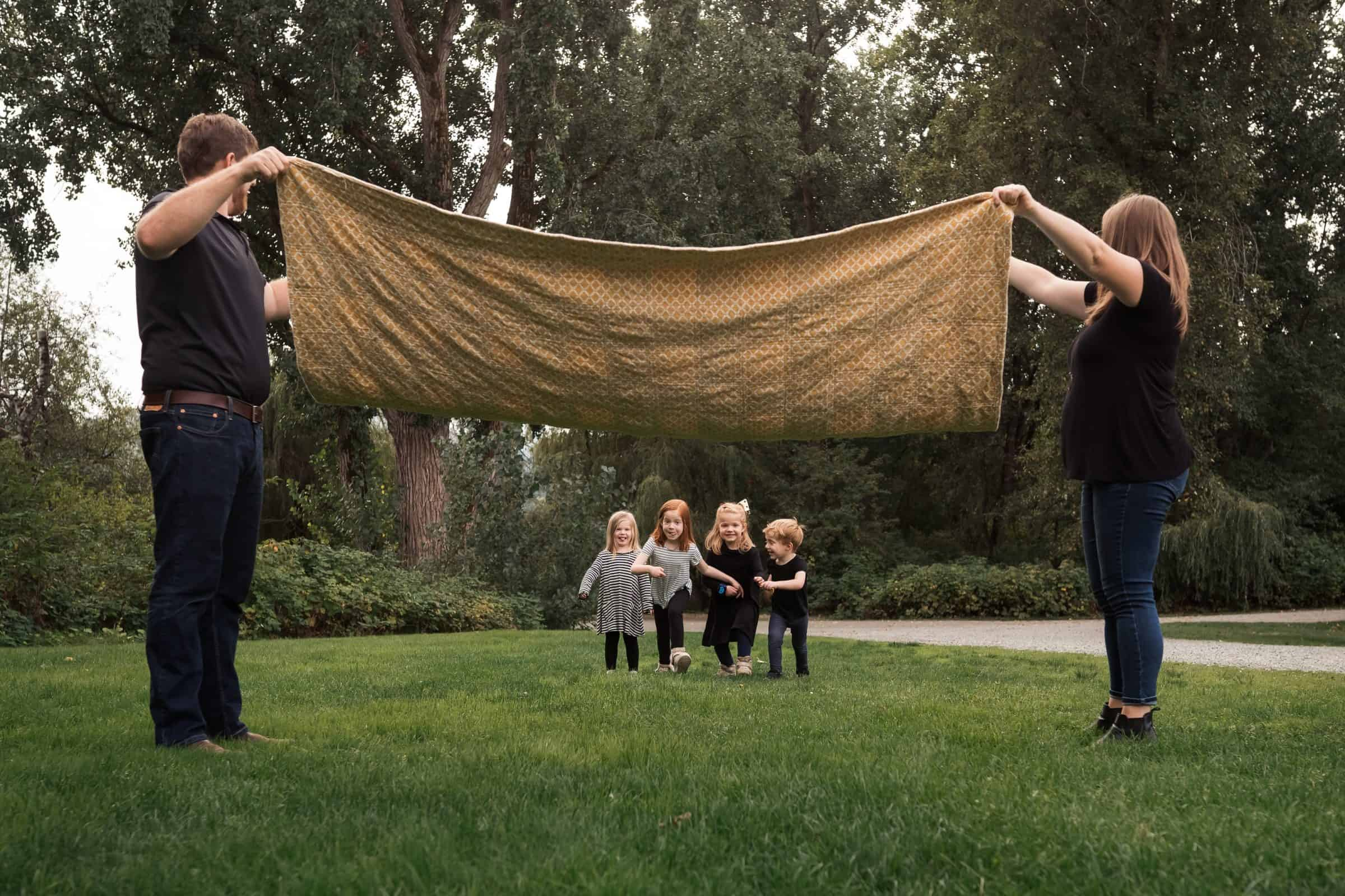four siblings running under blanket held by parents