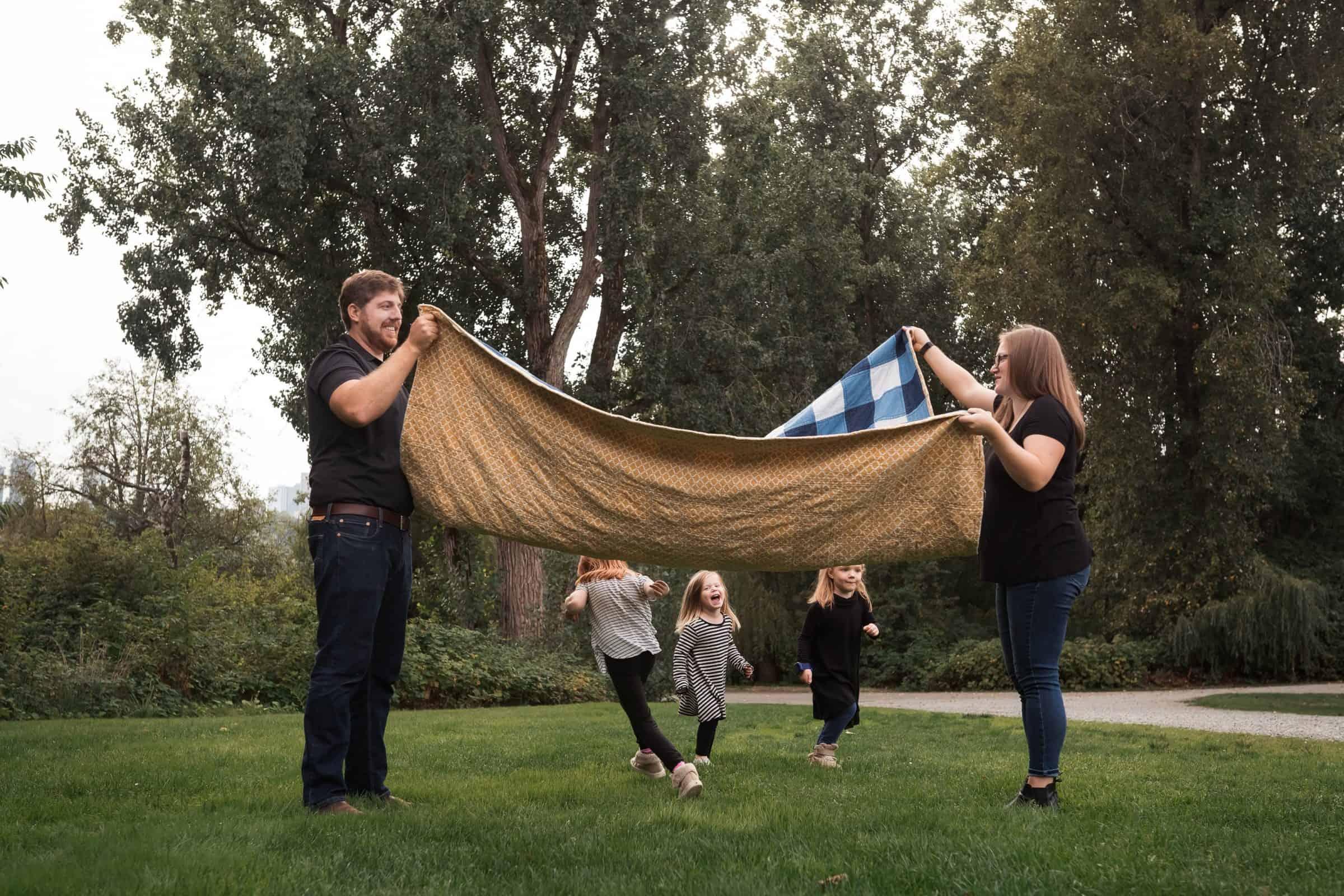 three little girls running under blanket held by parents