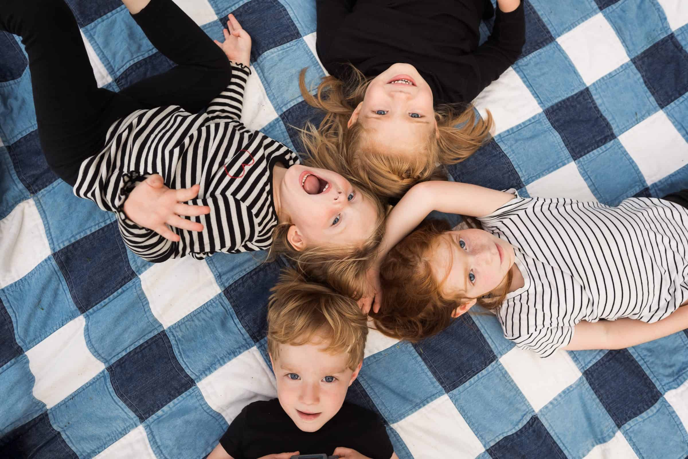 shot of four red-haired siblings from above on quilt