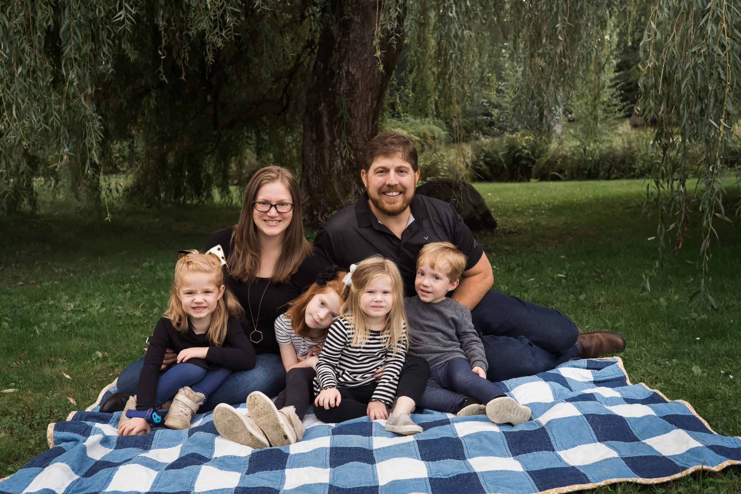 family with four red haired kids sitting on blanket smiling