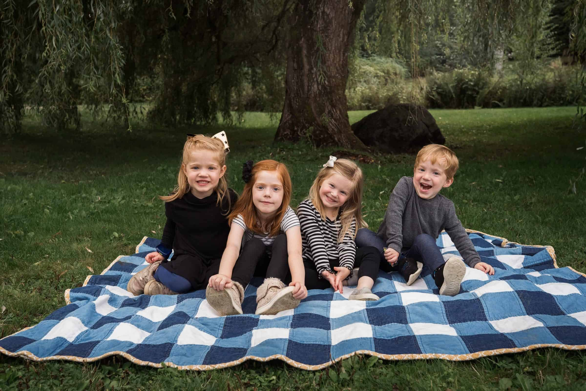 four red haired kids sitting on blanket smiling