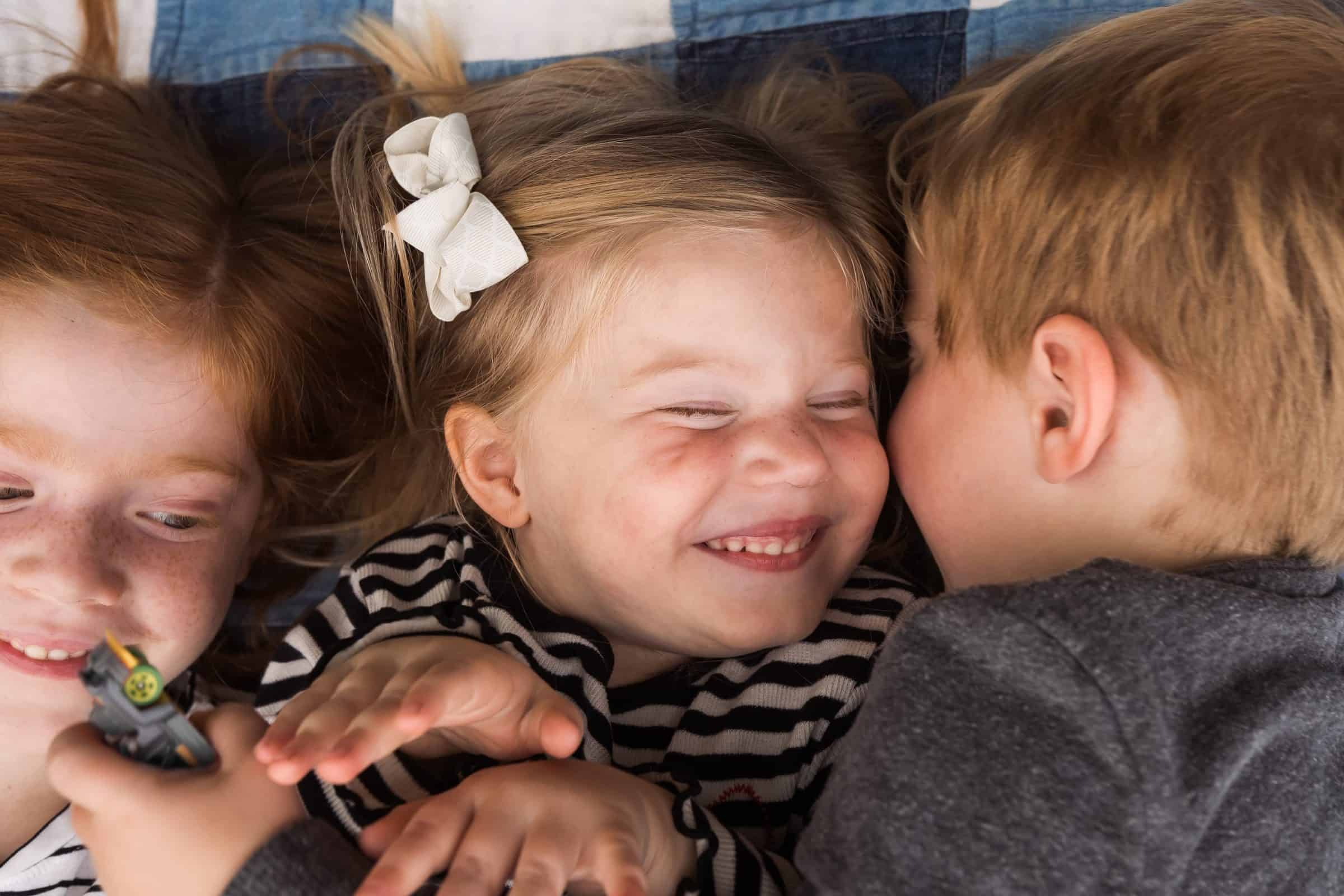 kids laying on blanket and laughing together