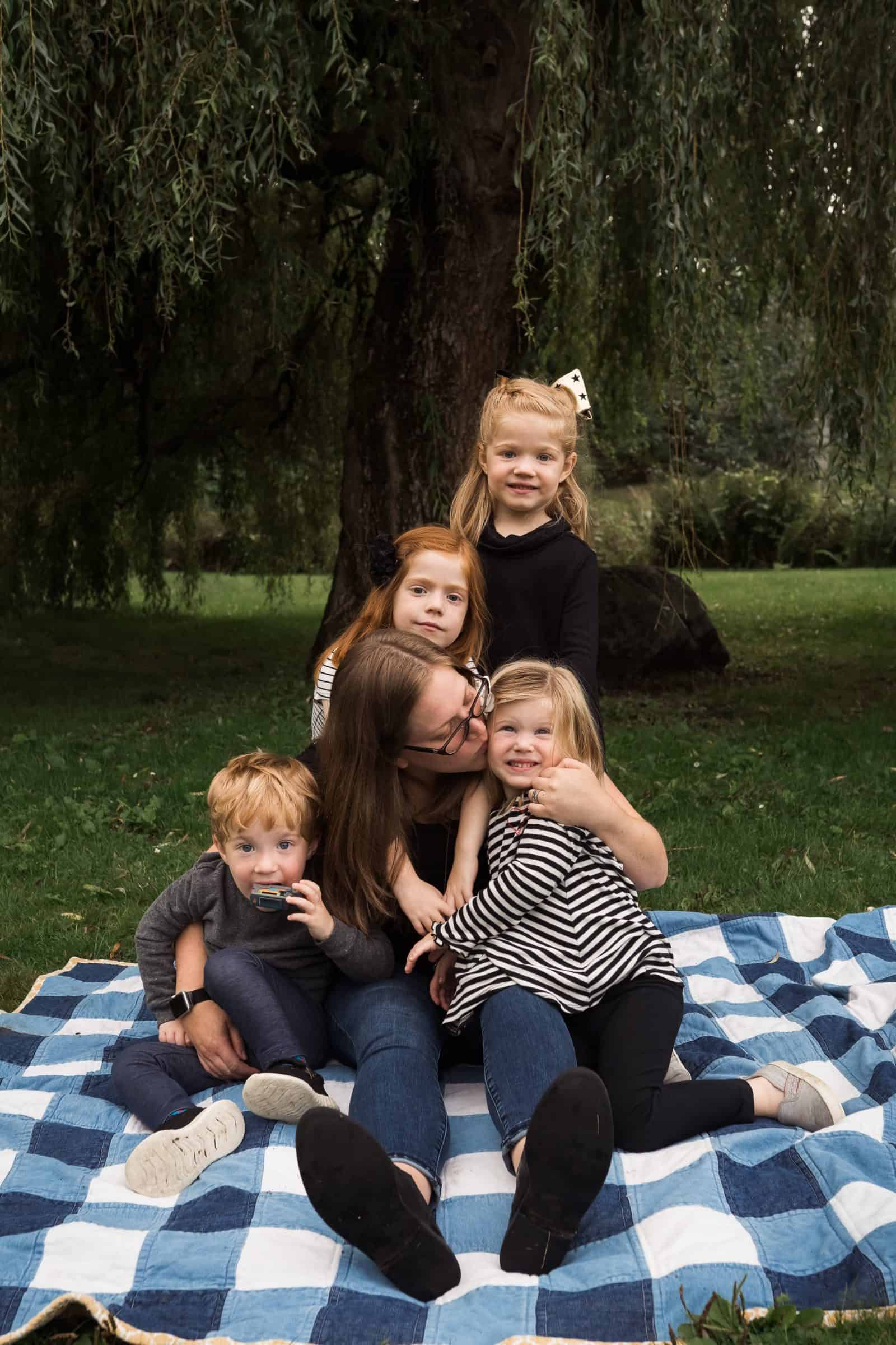 mom sitting on blacket with two girls and toddler boy-girl twins and snuggling them