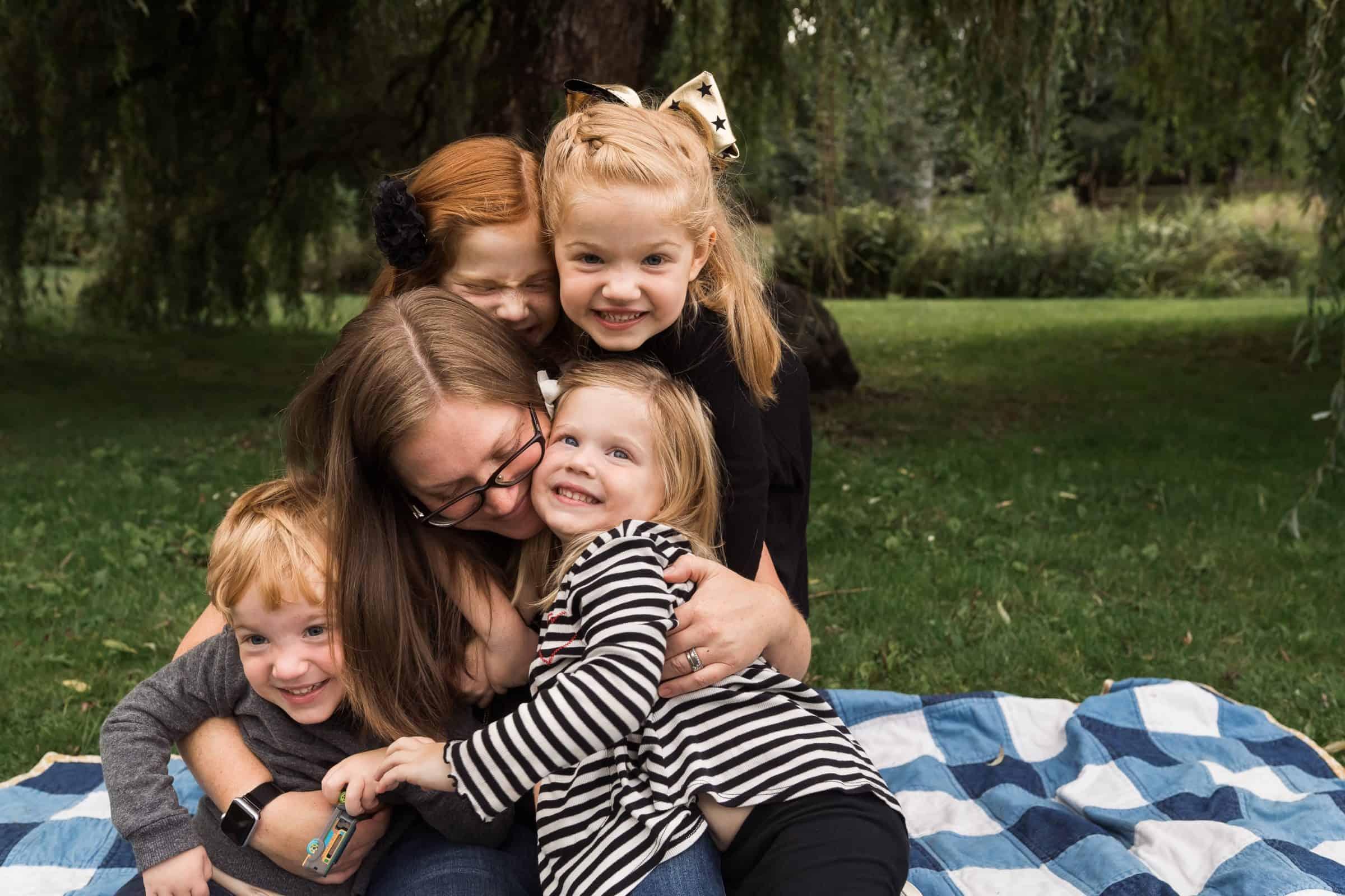 four little kids snuggling mom on blanket