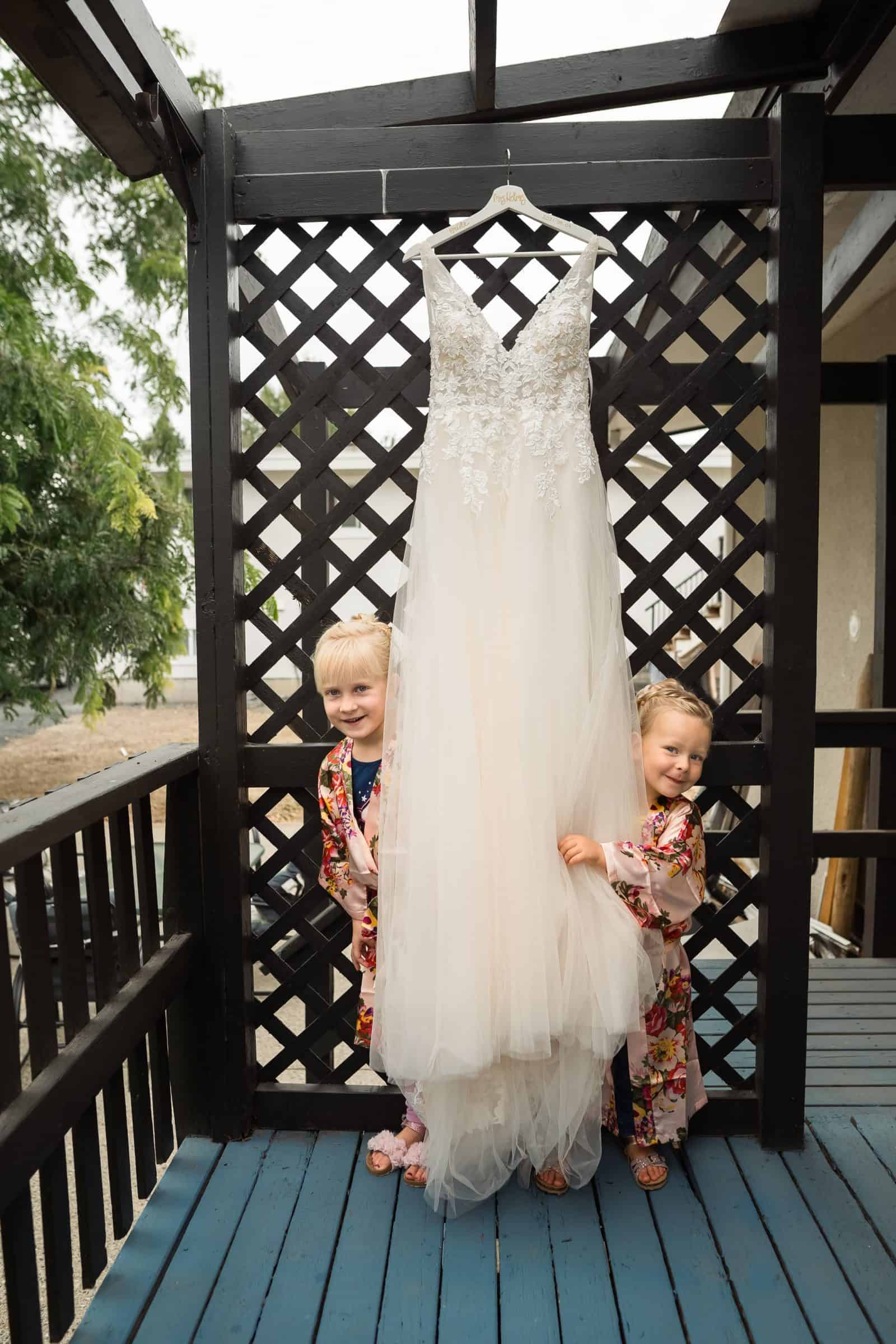 wedding dress handing with flower girls peeking out from behind it