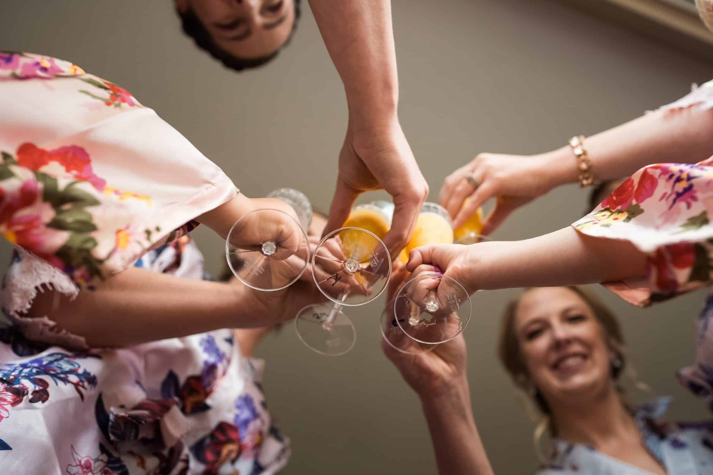 bridesmaids and bride holding cups and cheersing
