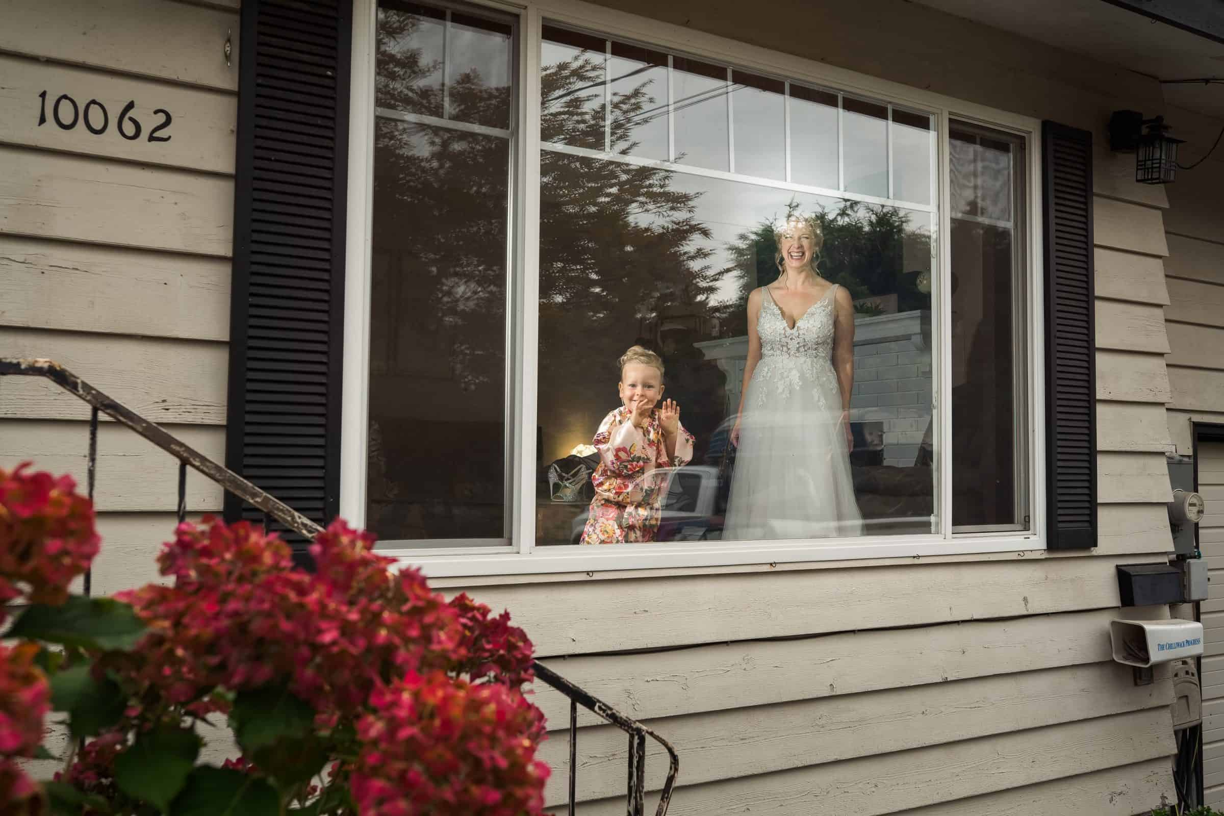 bride laughing and flower girl photobombing through window