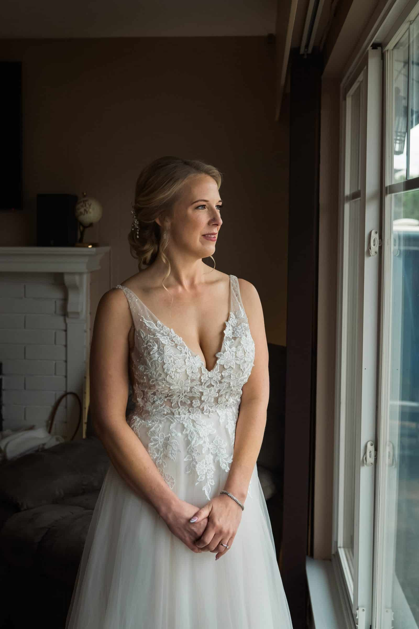 close up of bride looking out window in her wedding dress