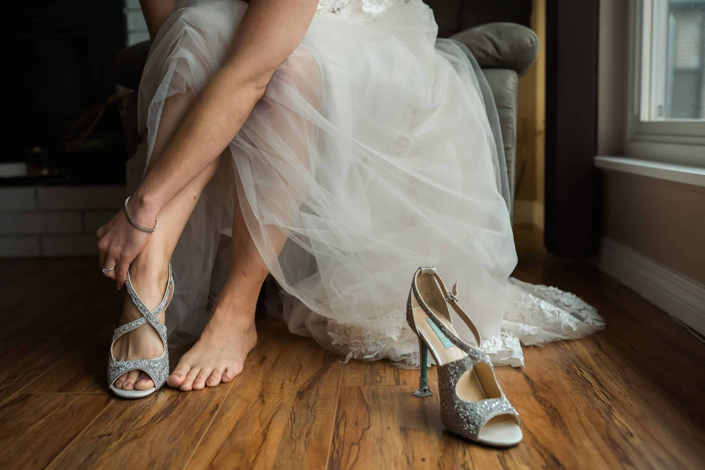 close up of bride putting on her shoes