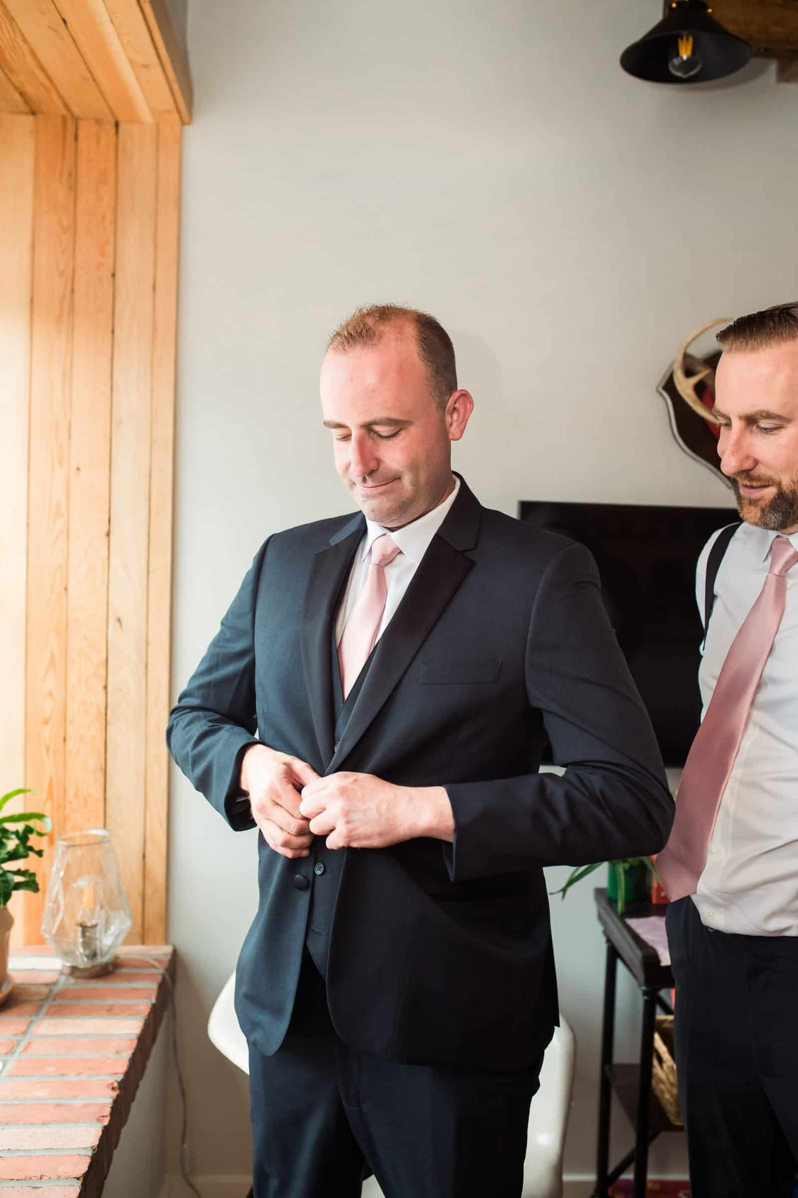 groom buttoning shirt with groomsman beside him
