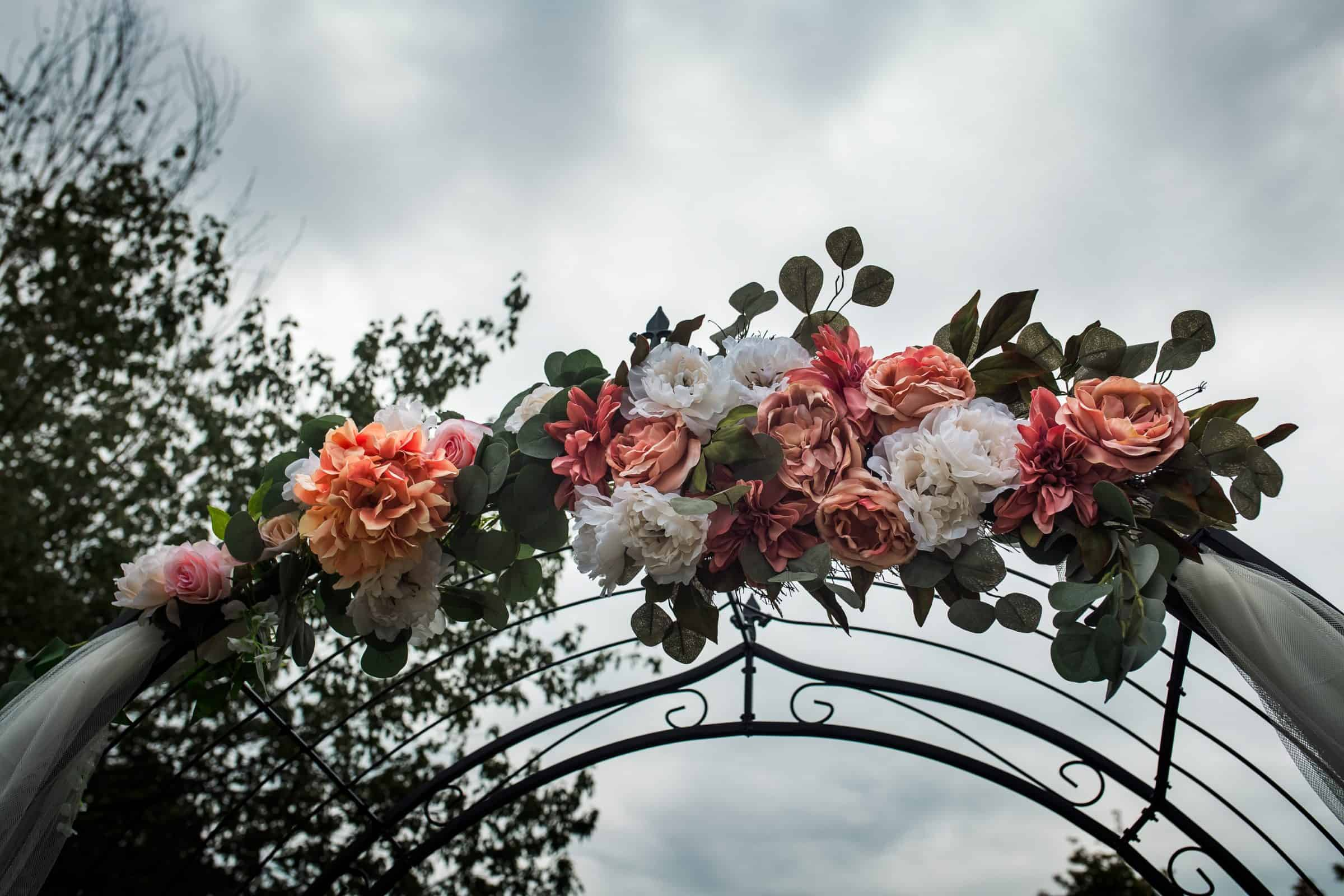 close up of flowers decorating wedding arch