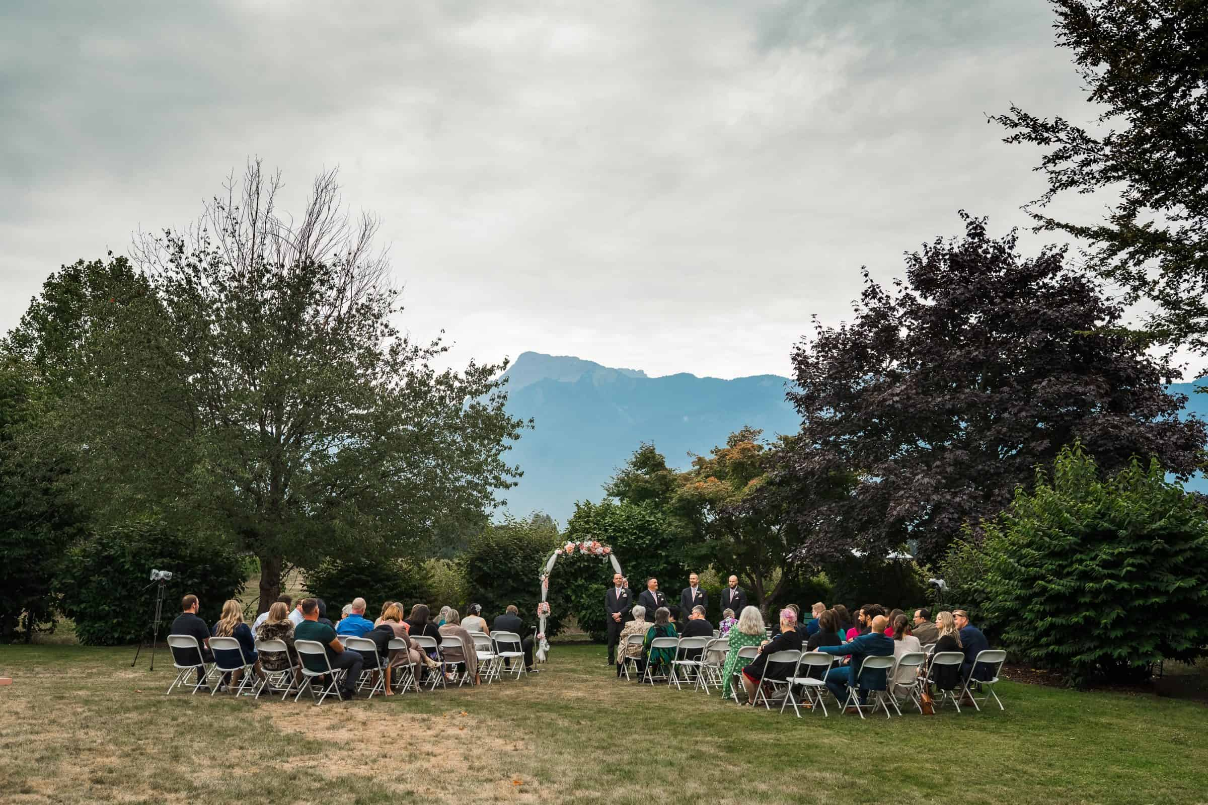 pullback of outdoor wedding ceremony with mountains in the background