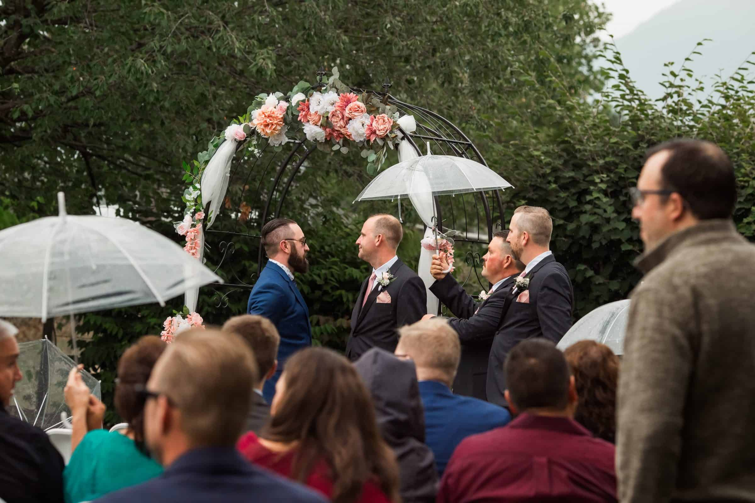 groomsman holding umbrella over groom in rain