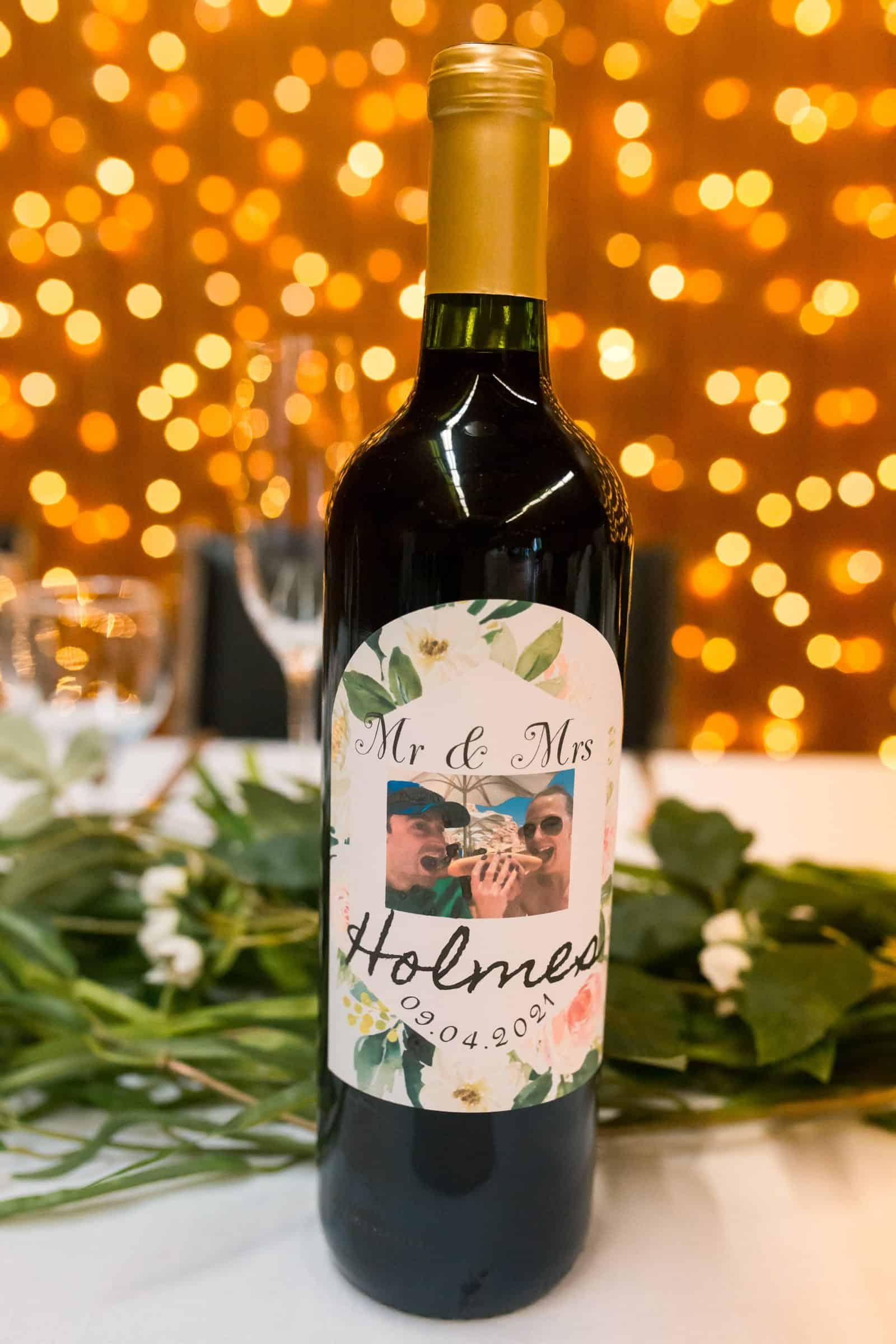 close up of customized wine bottle label on head table with bokeh in background