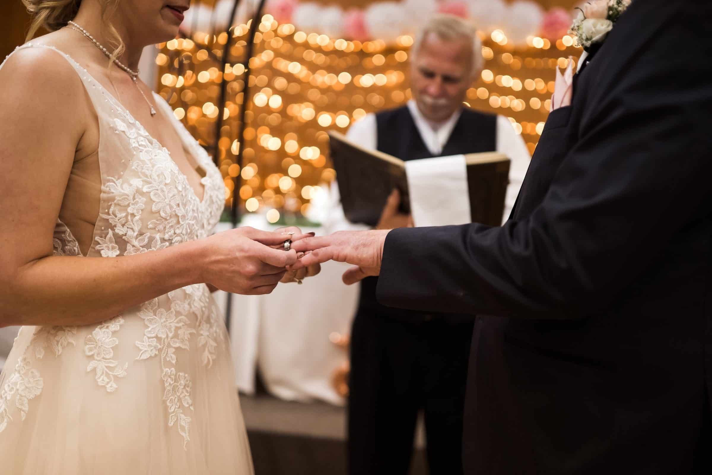close up of bride putting on groom's ring