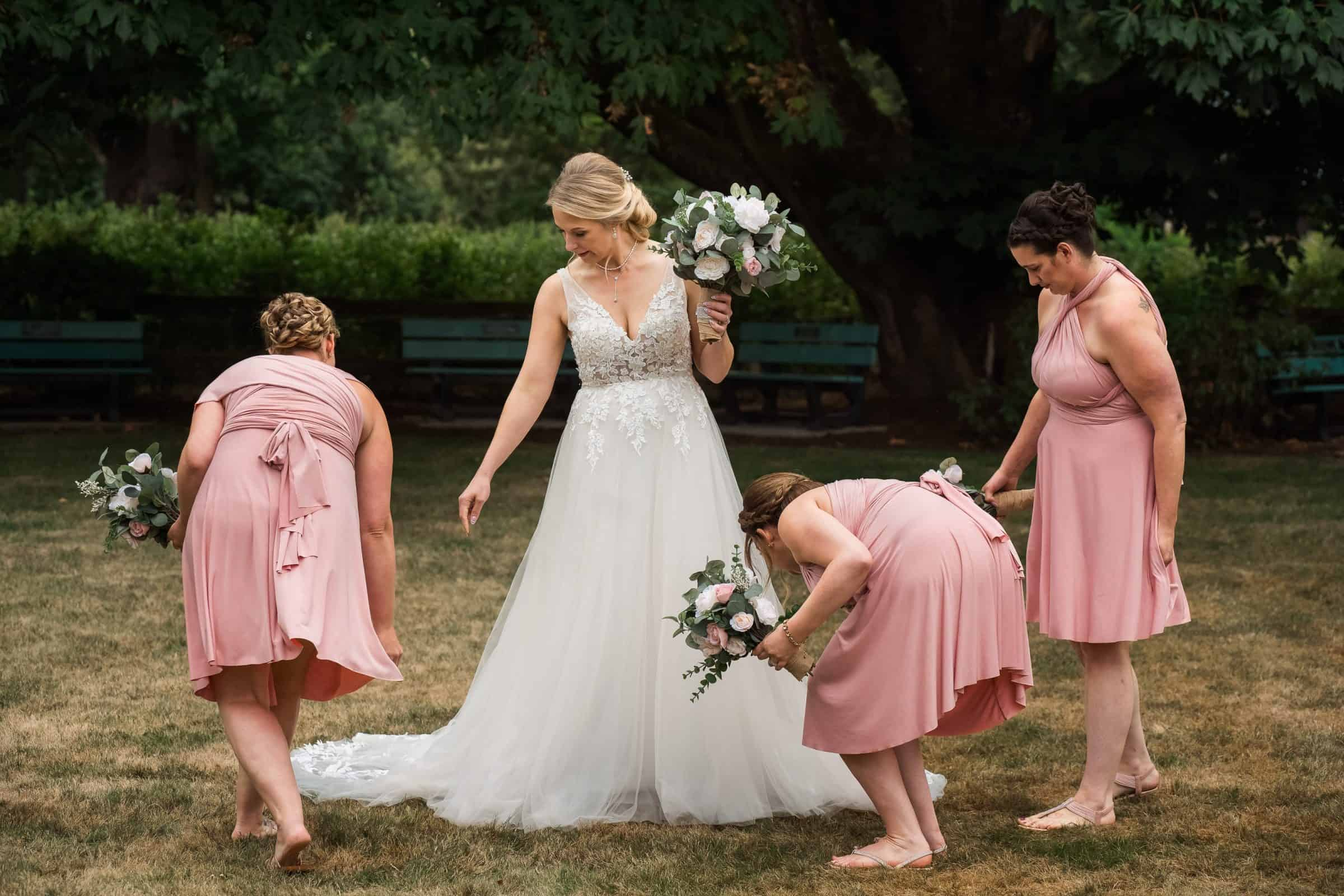 bridal party girls helping arrange bride's dress