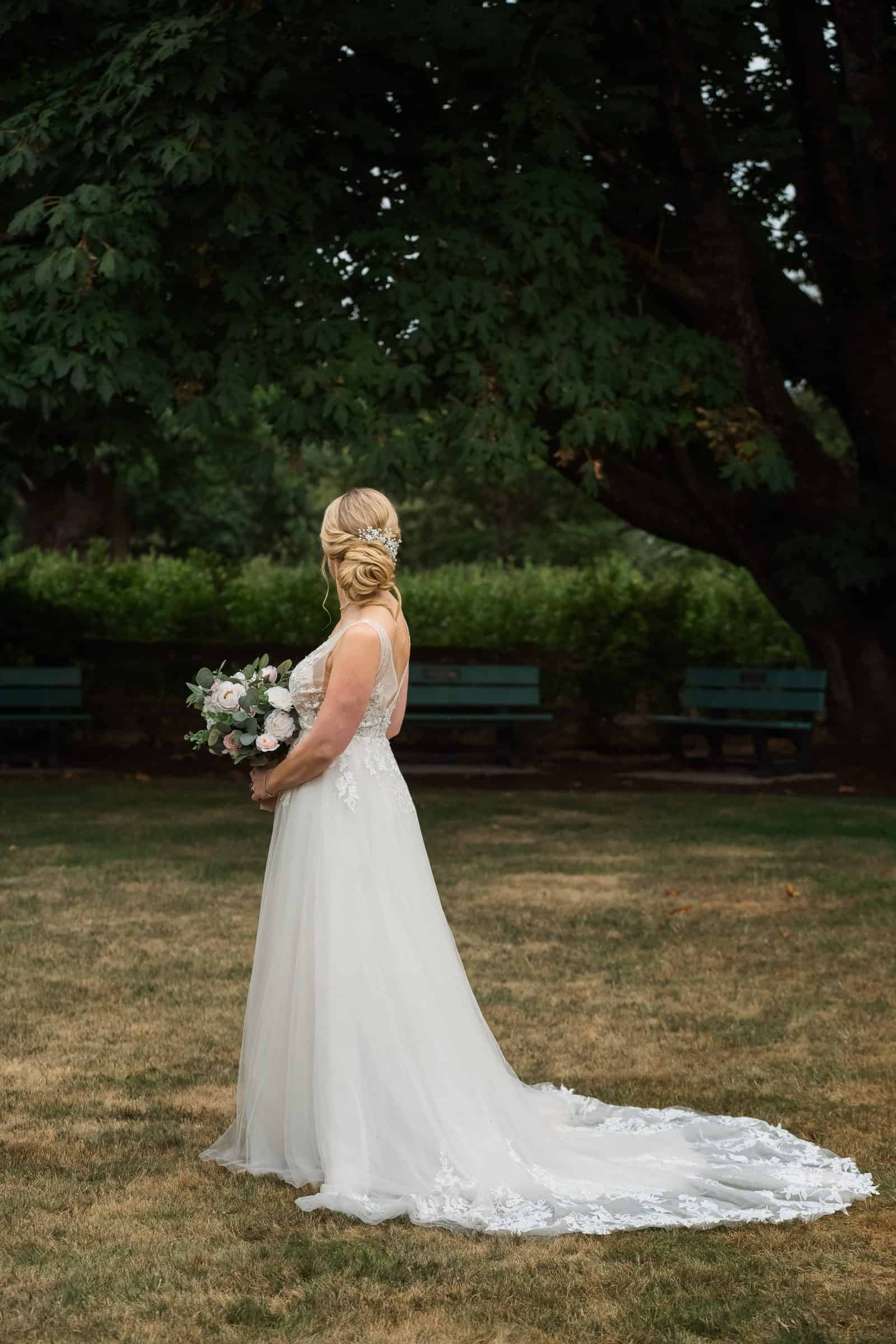 portrait of bride in wedding dress with flowers highlighting her updo