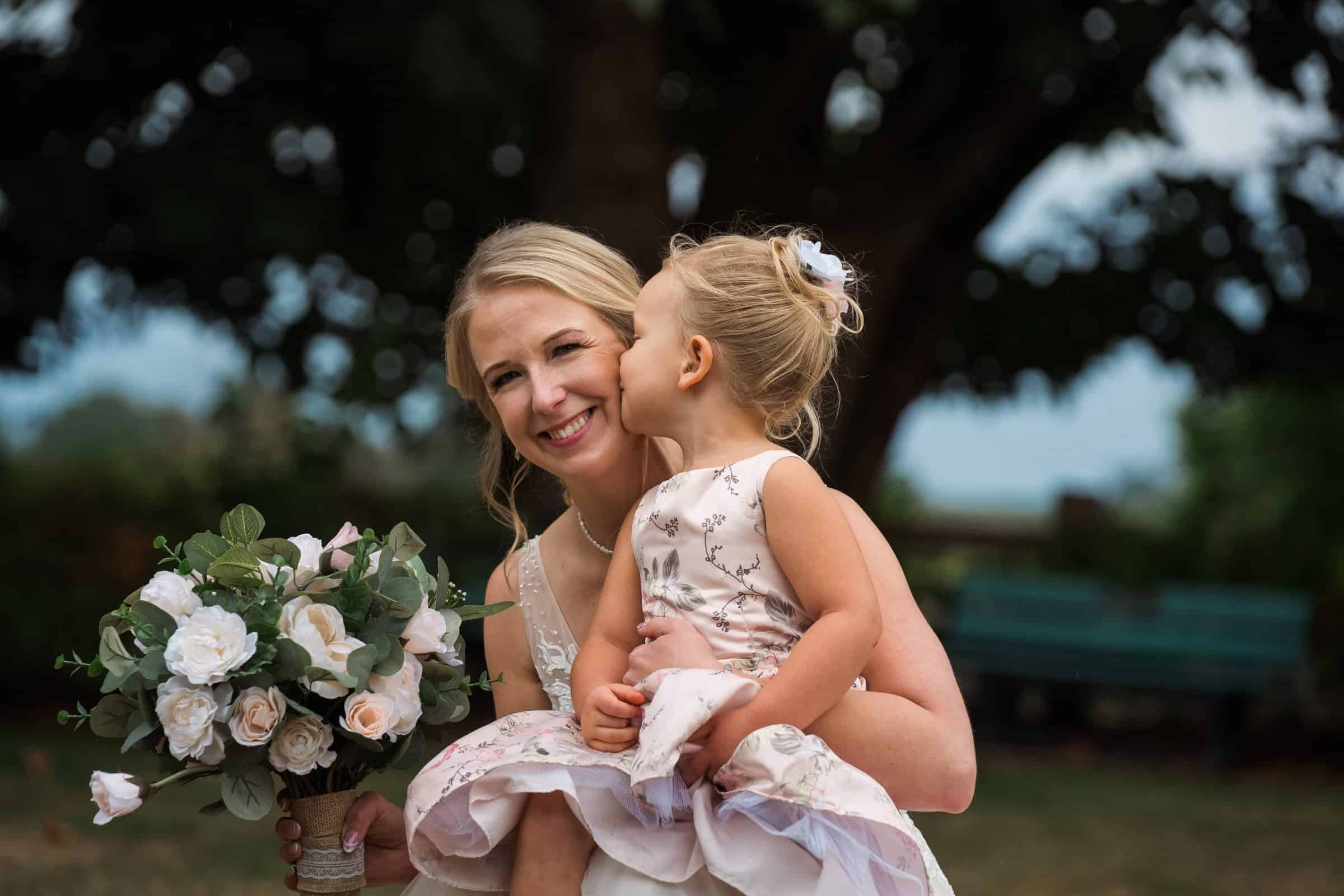 bride holding flower girl and being kissed on the cheek