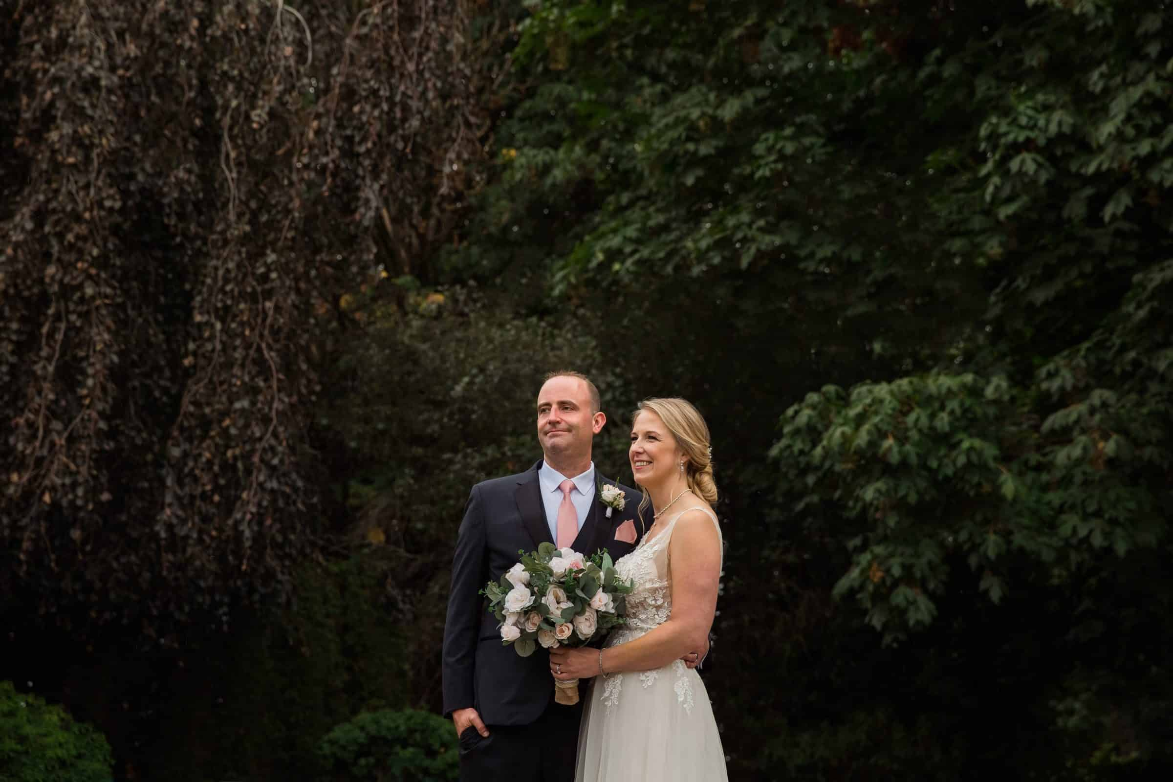 bride and groom standing together surrounded by trees