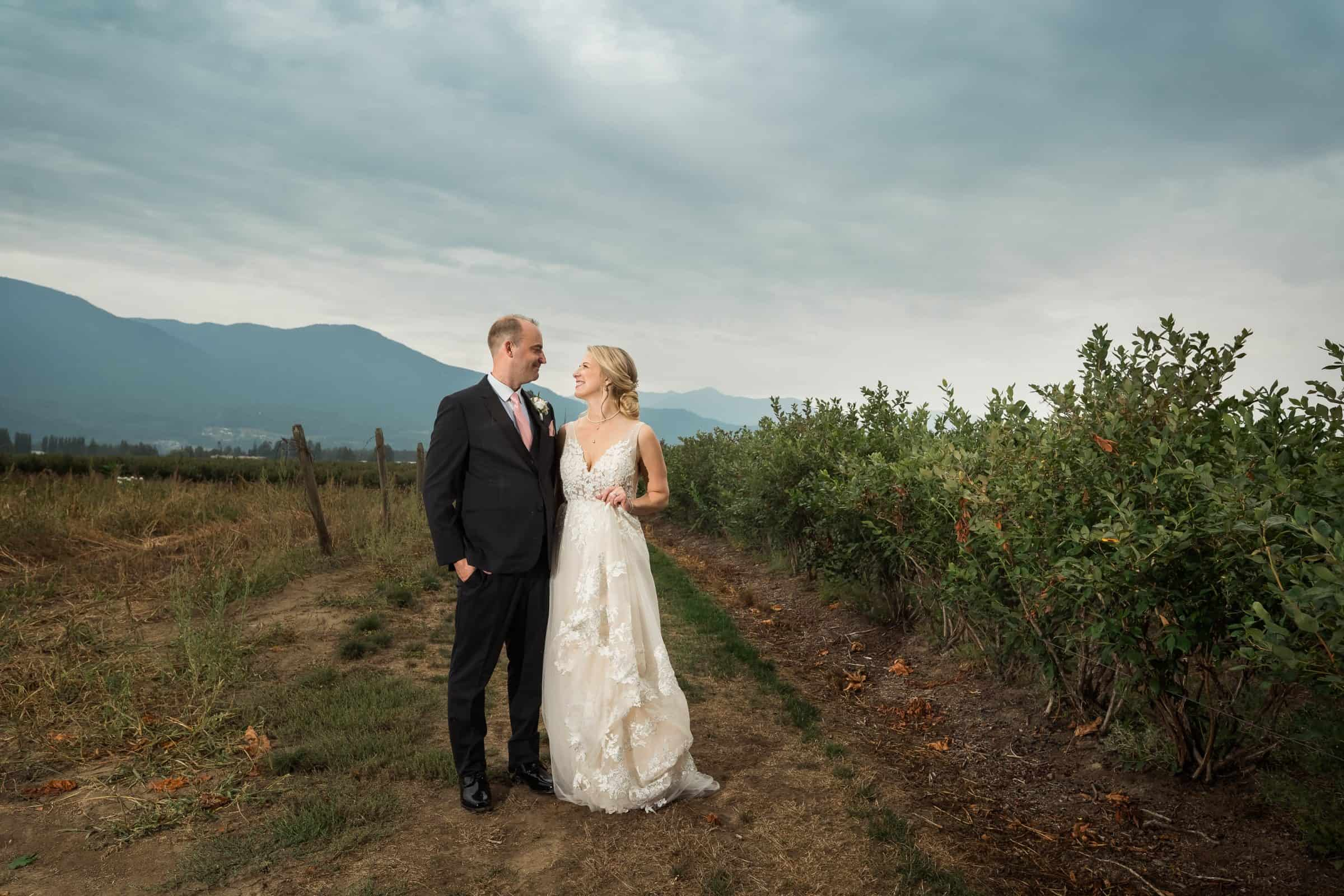 bride and groom looking at each other in field with mountains behind