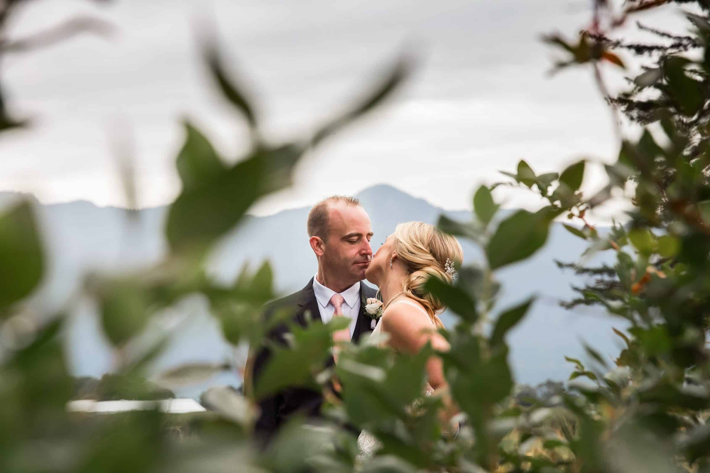 bride and groom kissing through blueberry leaves with mountains in background