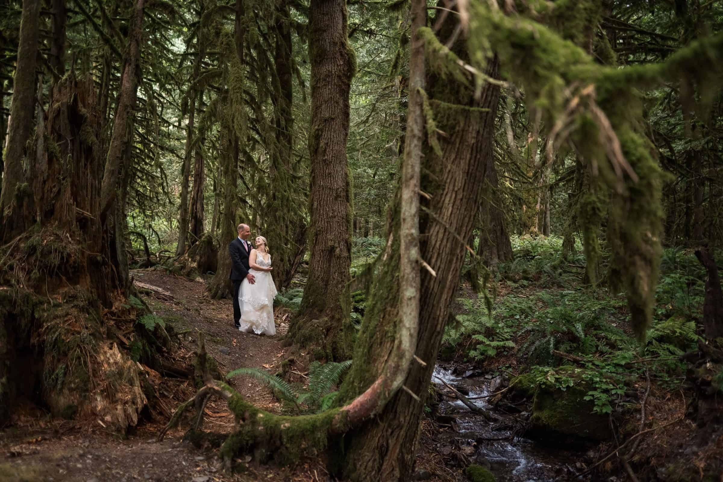 bride and groom holding each other and laughing in forest with river