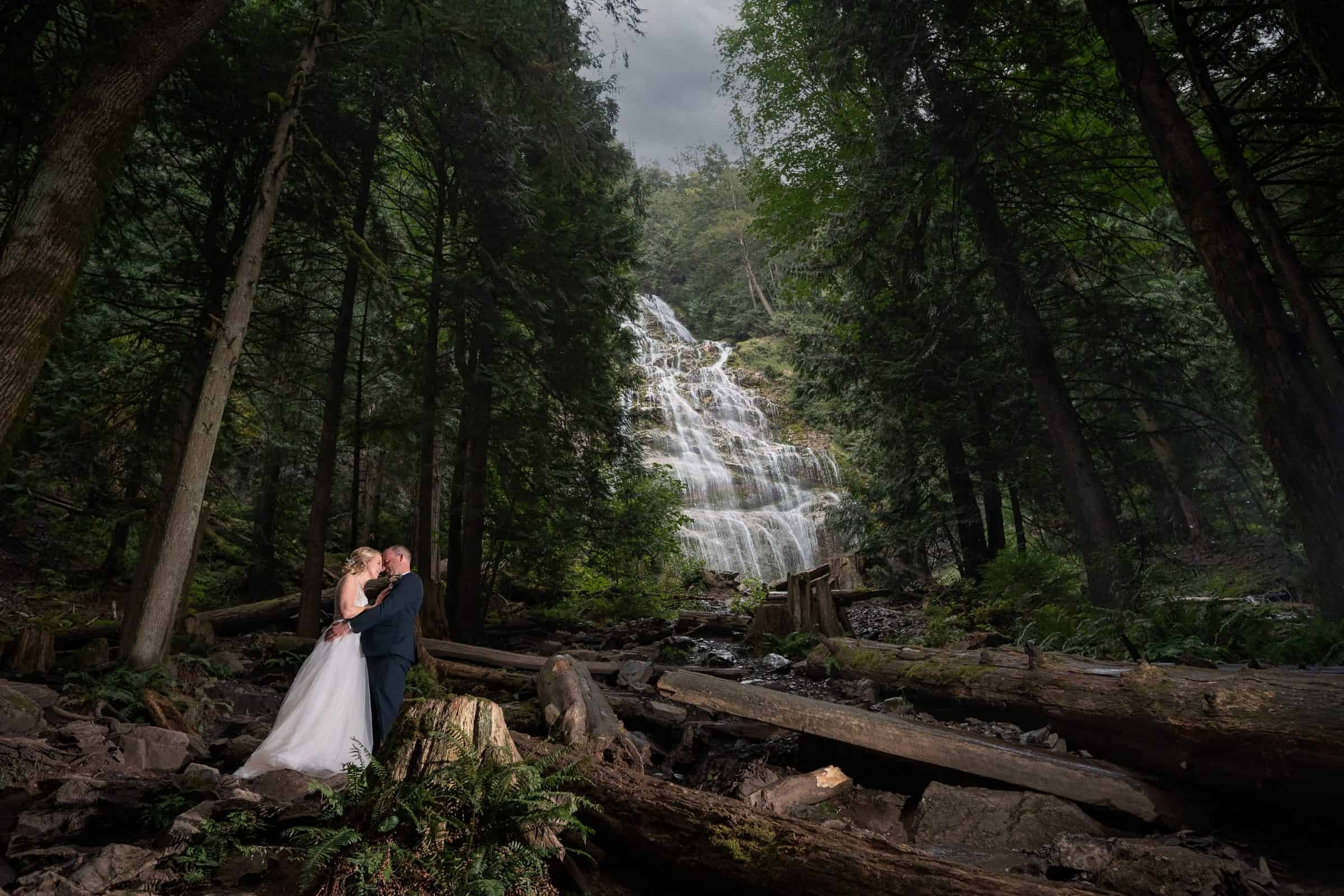 bride and groom holding each other with bridal falls in background