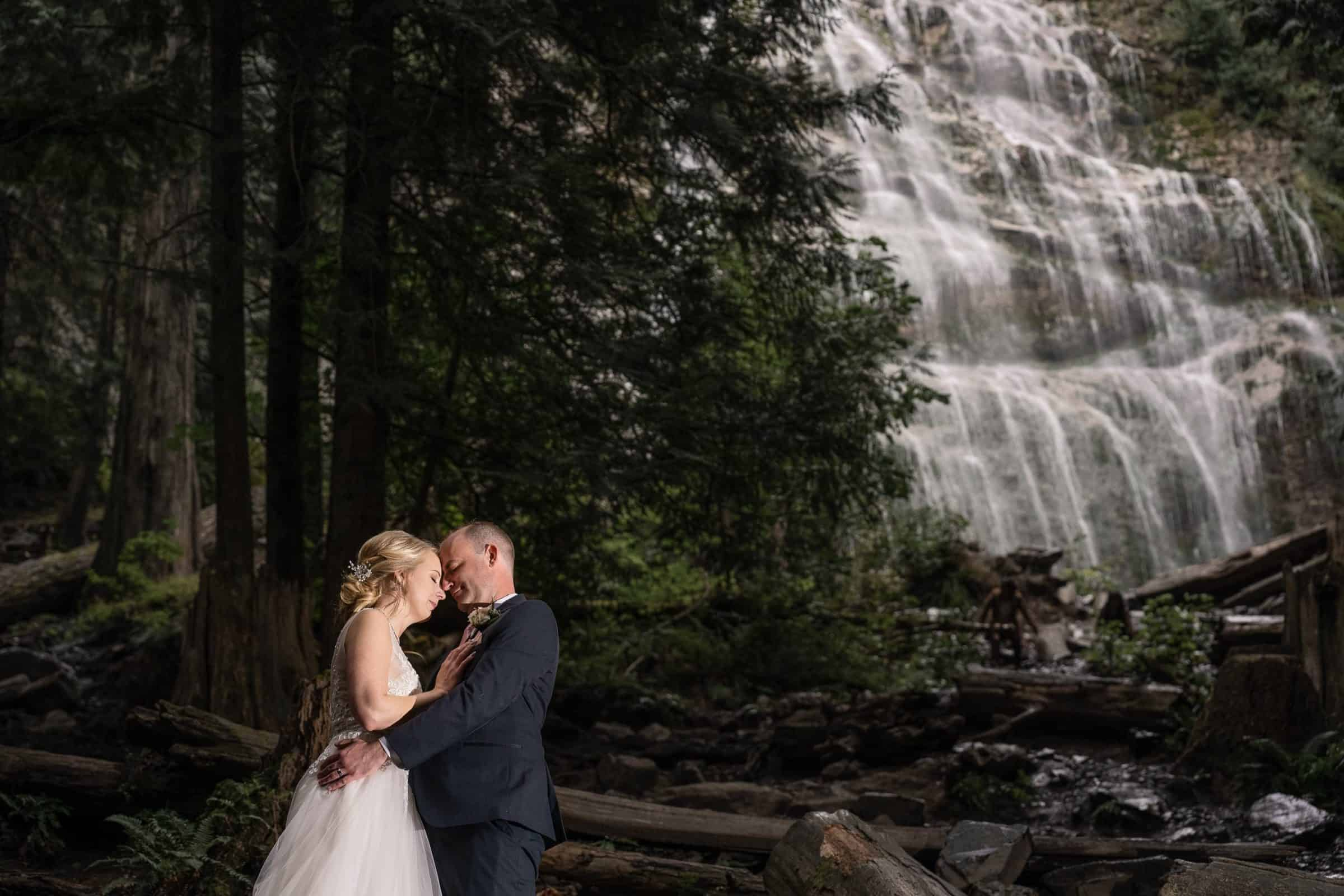 close up of bride and groom holding each other with bridal falls in background