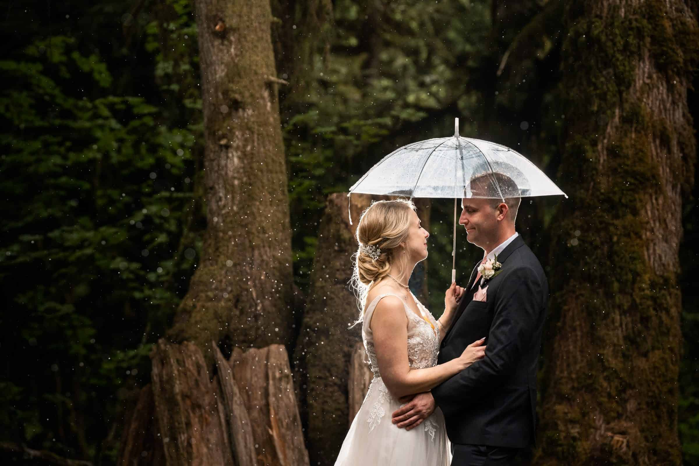 bride and groom holding each other under umbrella in the rain