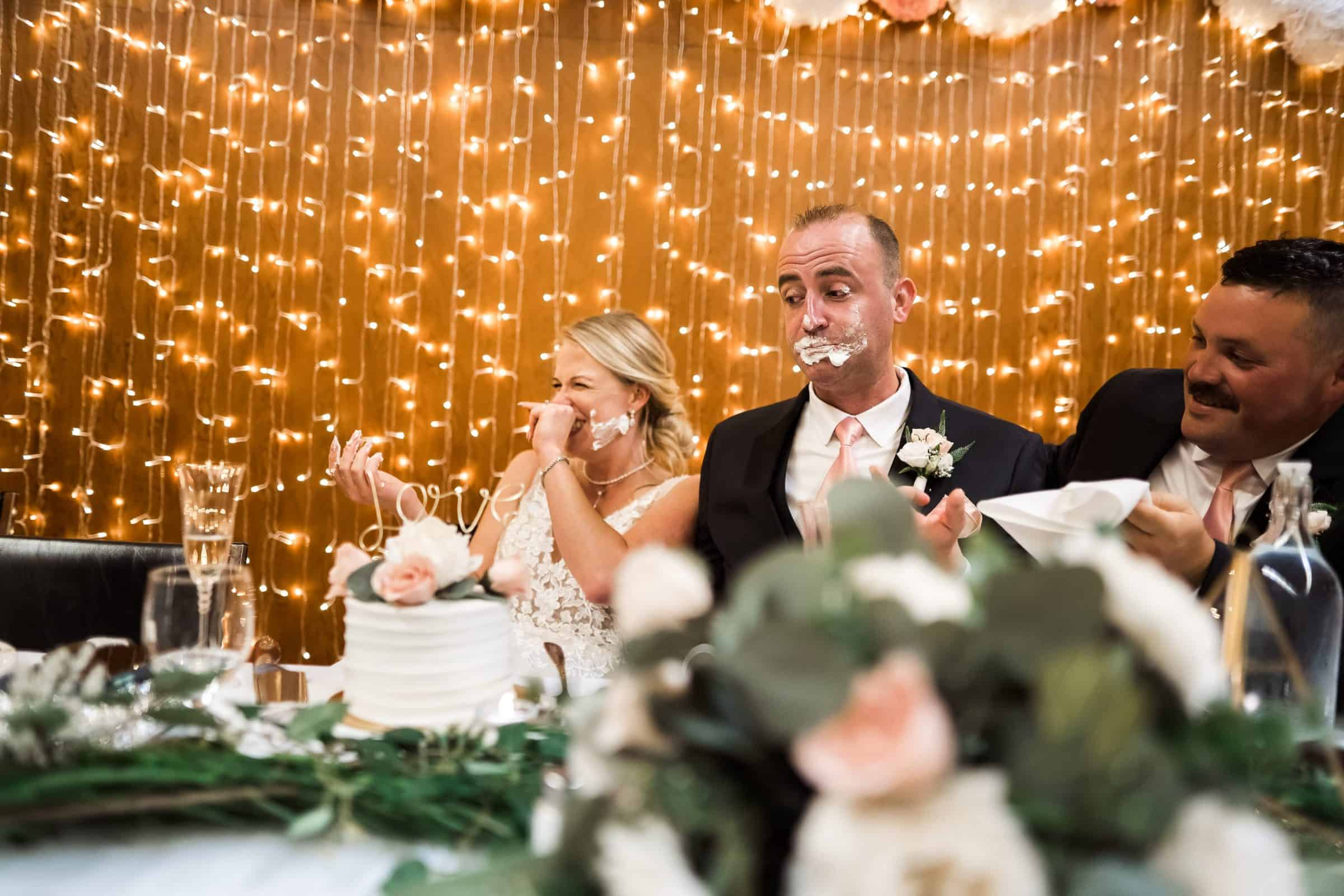 bride smashing wedding cake into grooms face and the laughing