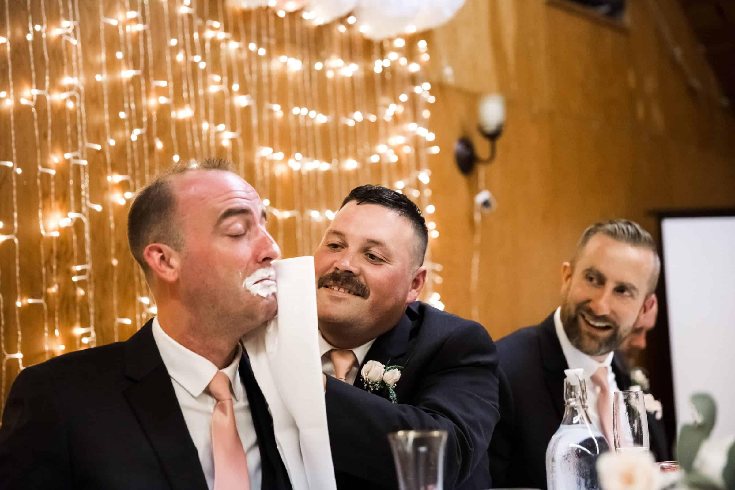groomsman wiping cake off groom's face