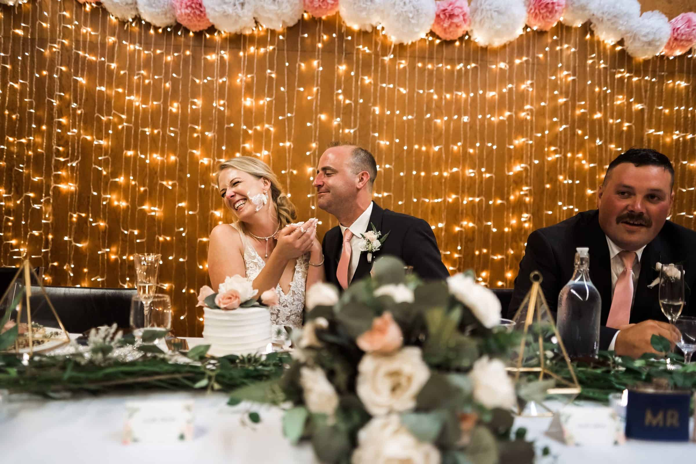 bride laughing after groom puts cake on her face