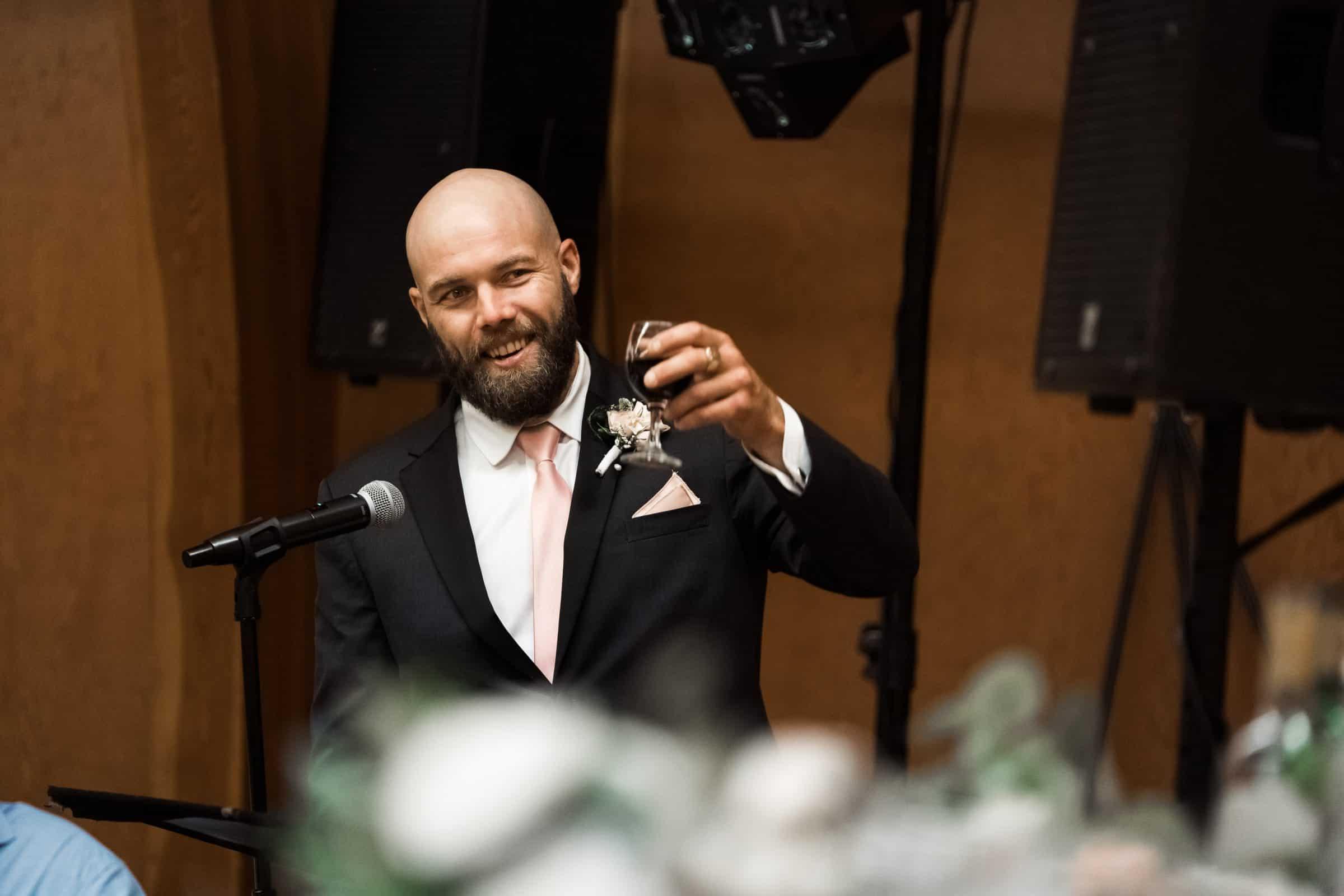 groomsman lifting glass in cheers