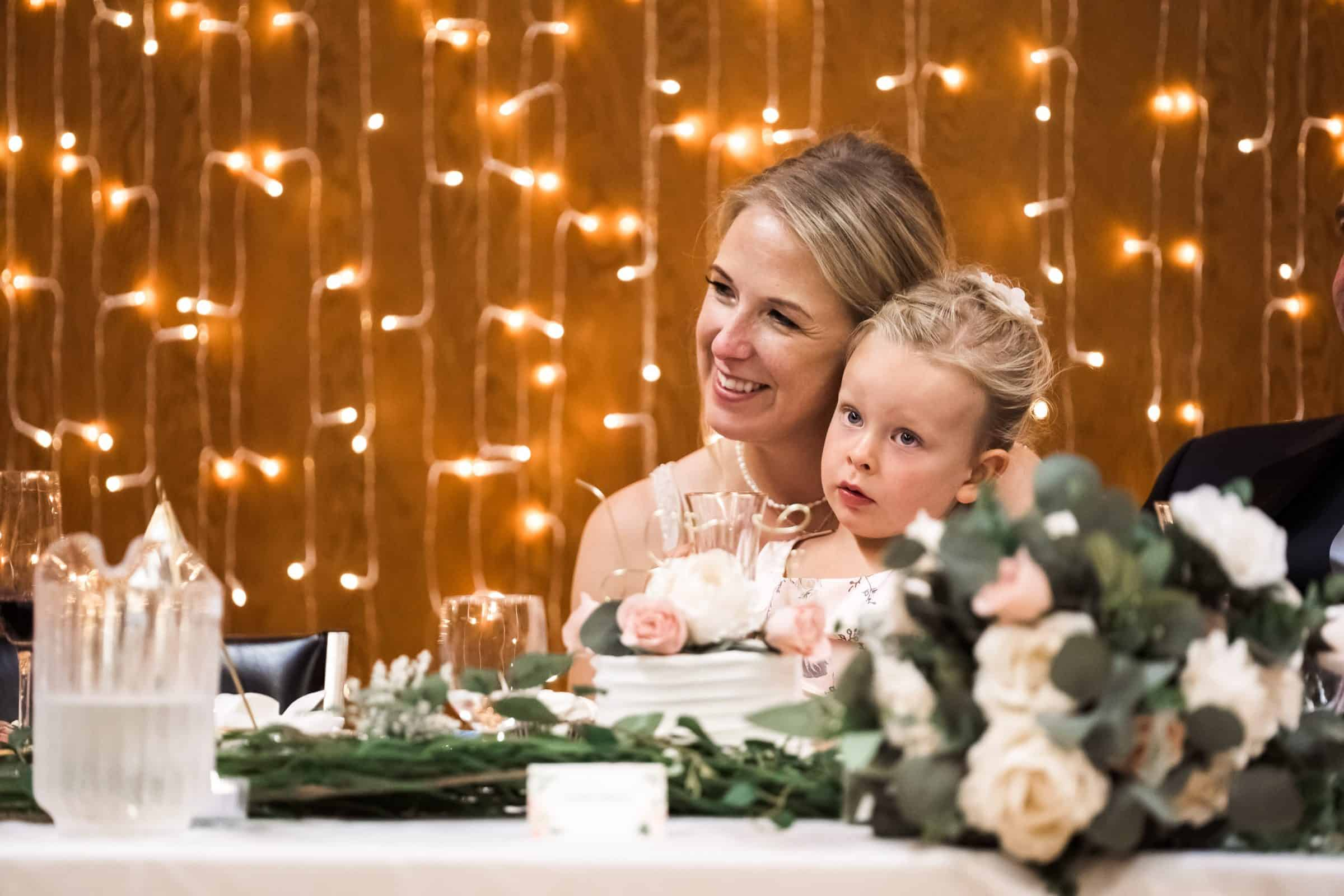flower girl sitting on bride's lap at head table