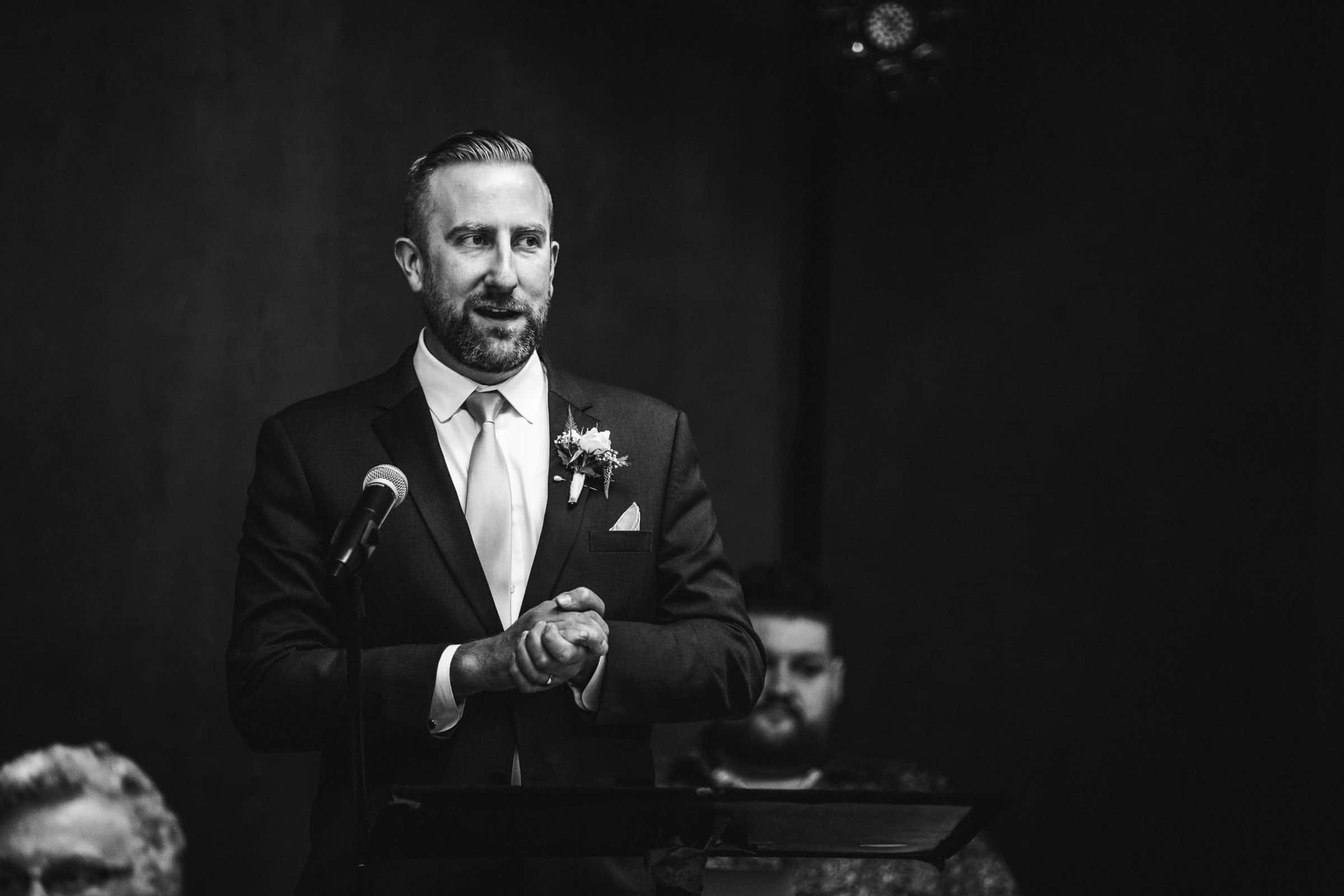 black and white image of groomsman giving a speech