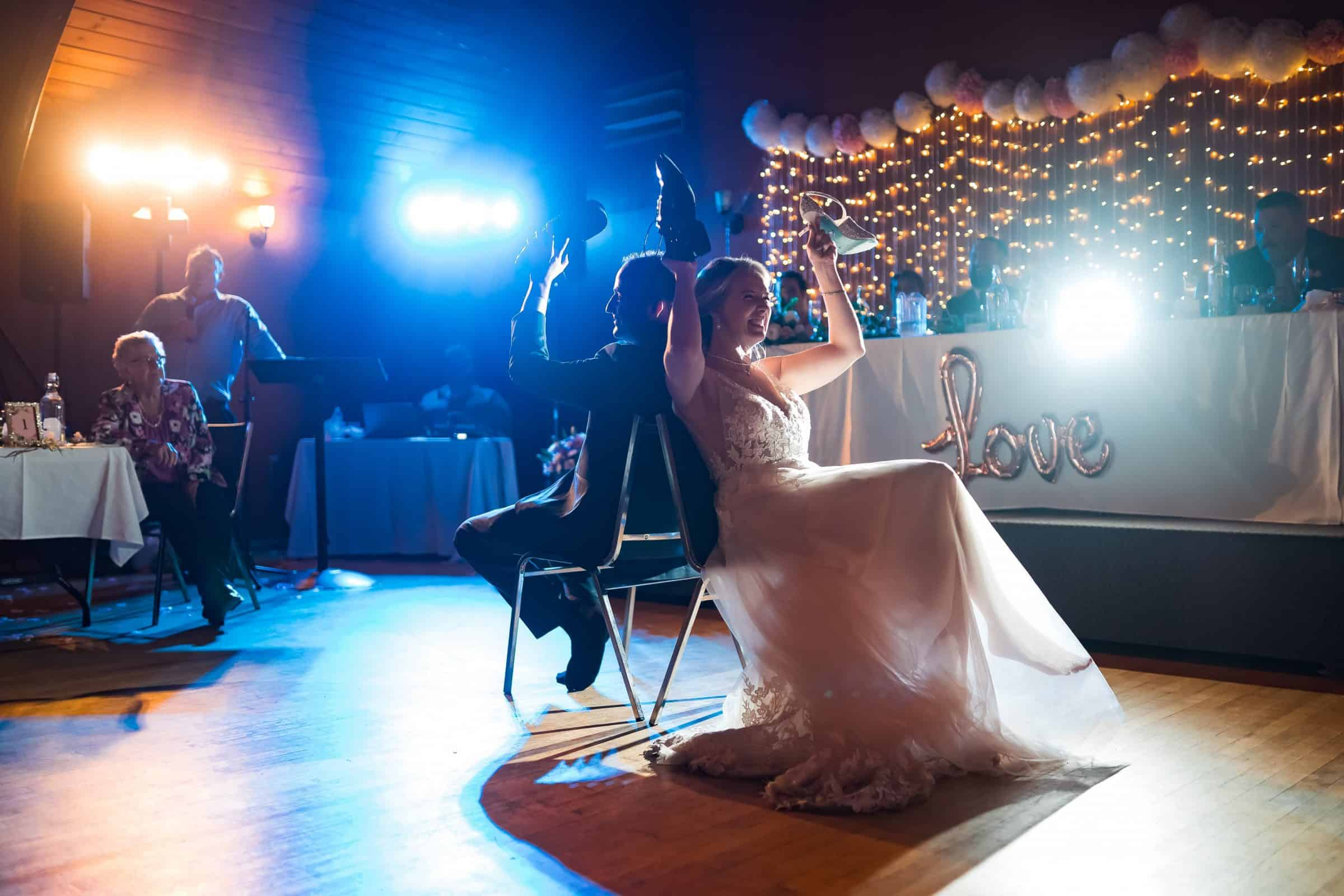 bride and groom playing shoe game with orange and blue and white lights