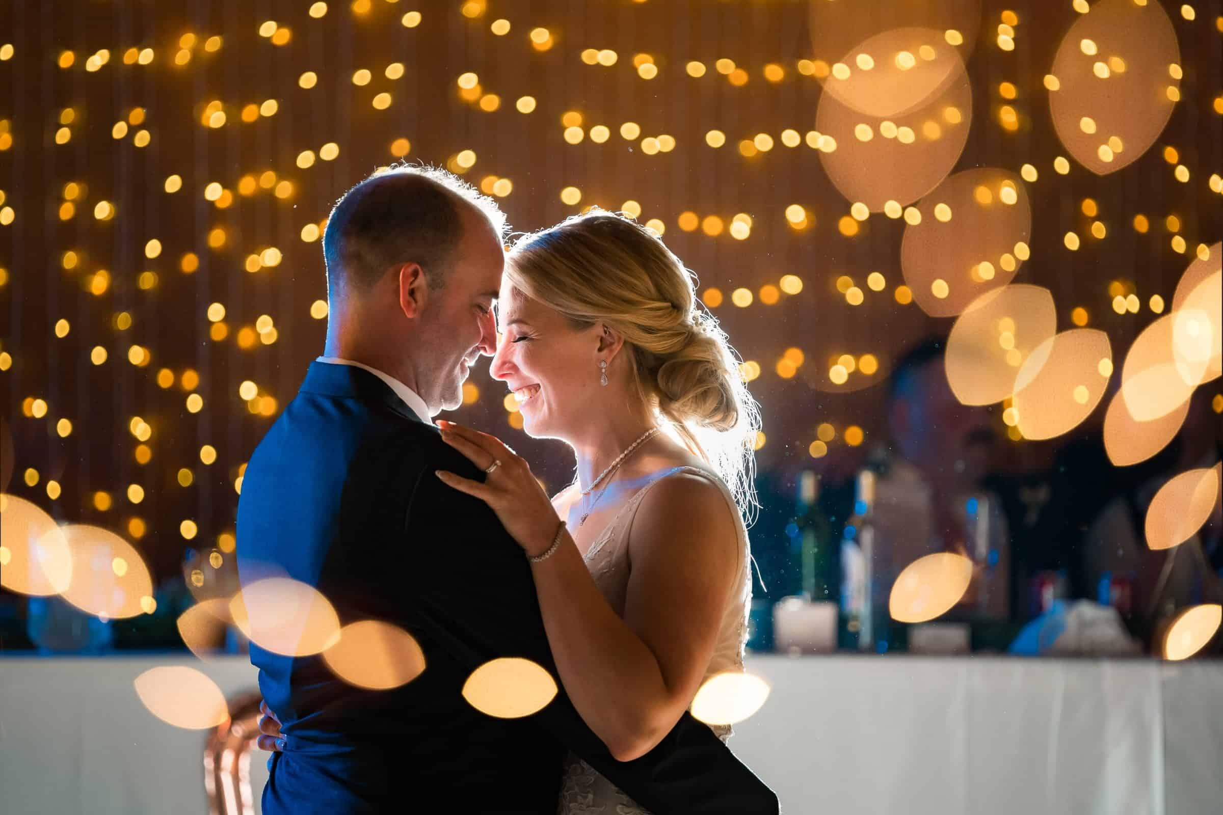 bride and groom having first dance surrounded by bokeh lights